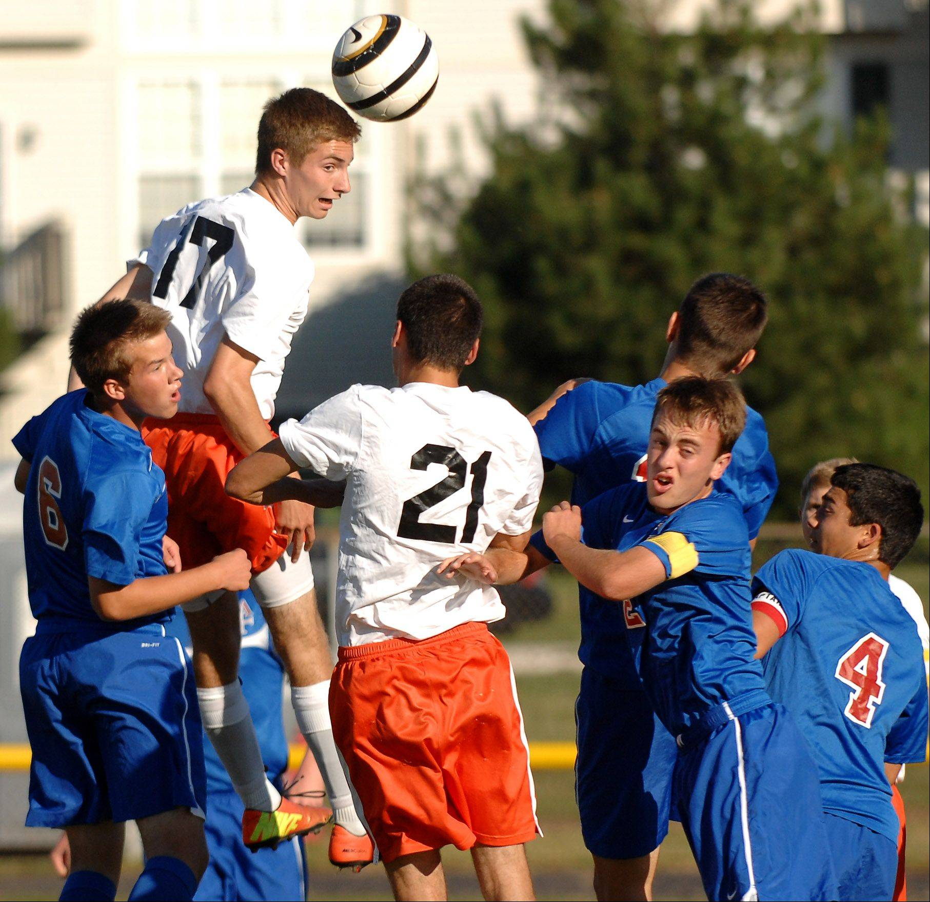 St. Charles East�s Evan DiLeonardi wins a header on a corner kick against Marmion during Thursday�s game in St. Charles.