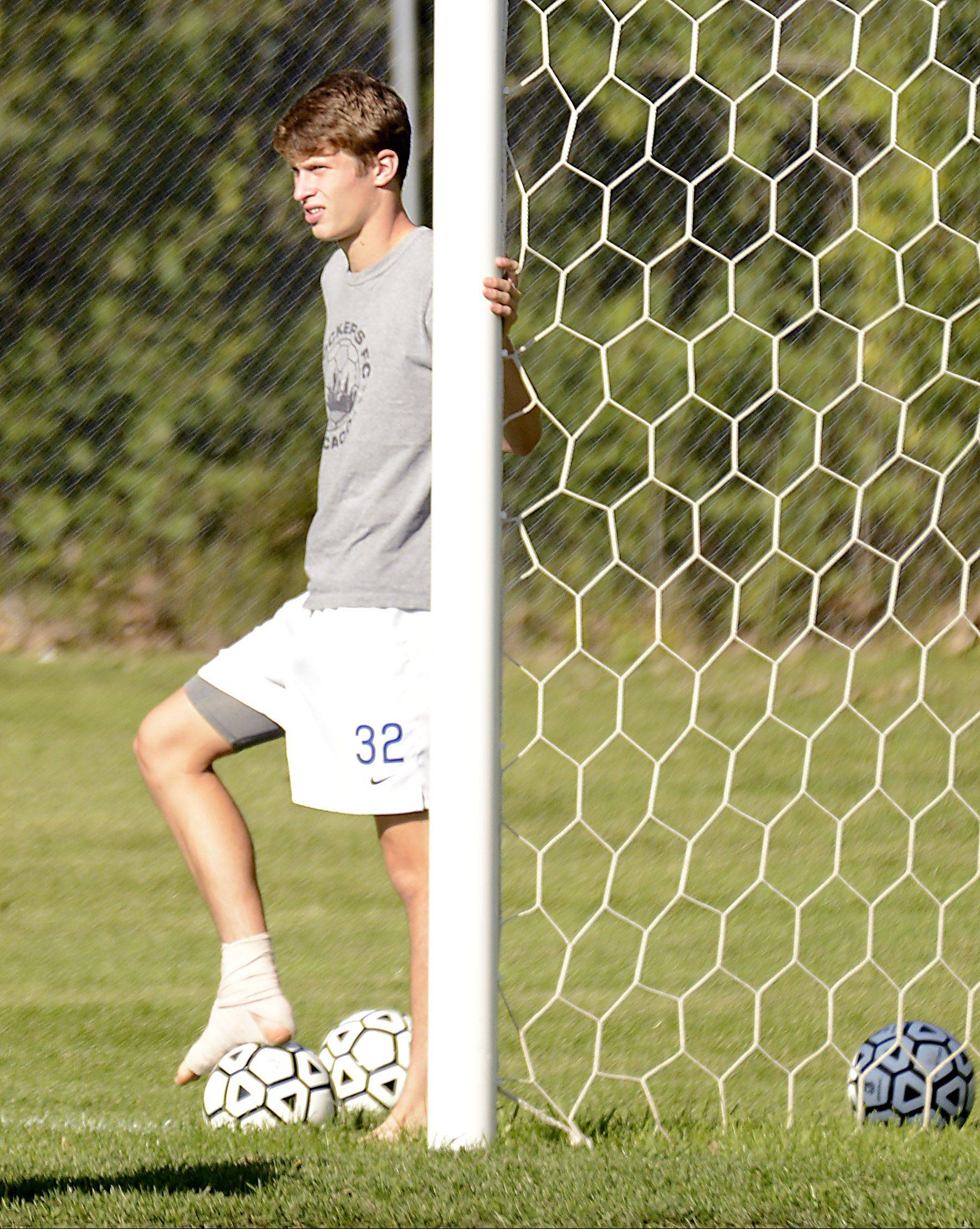Ben Stone sits out Dundee-Crown boys soccer practice Tuesday after getting cleated earlier in the week in Carpentersville.