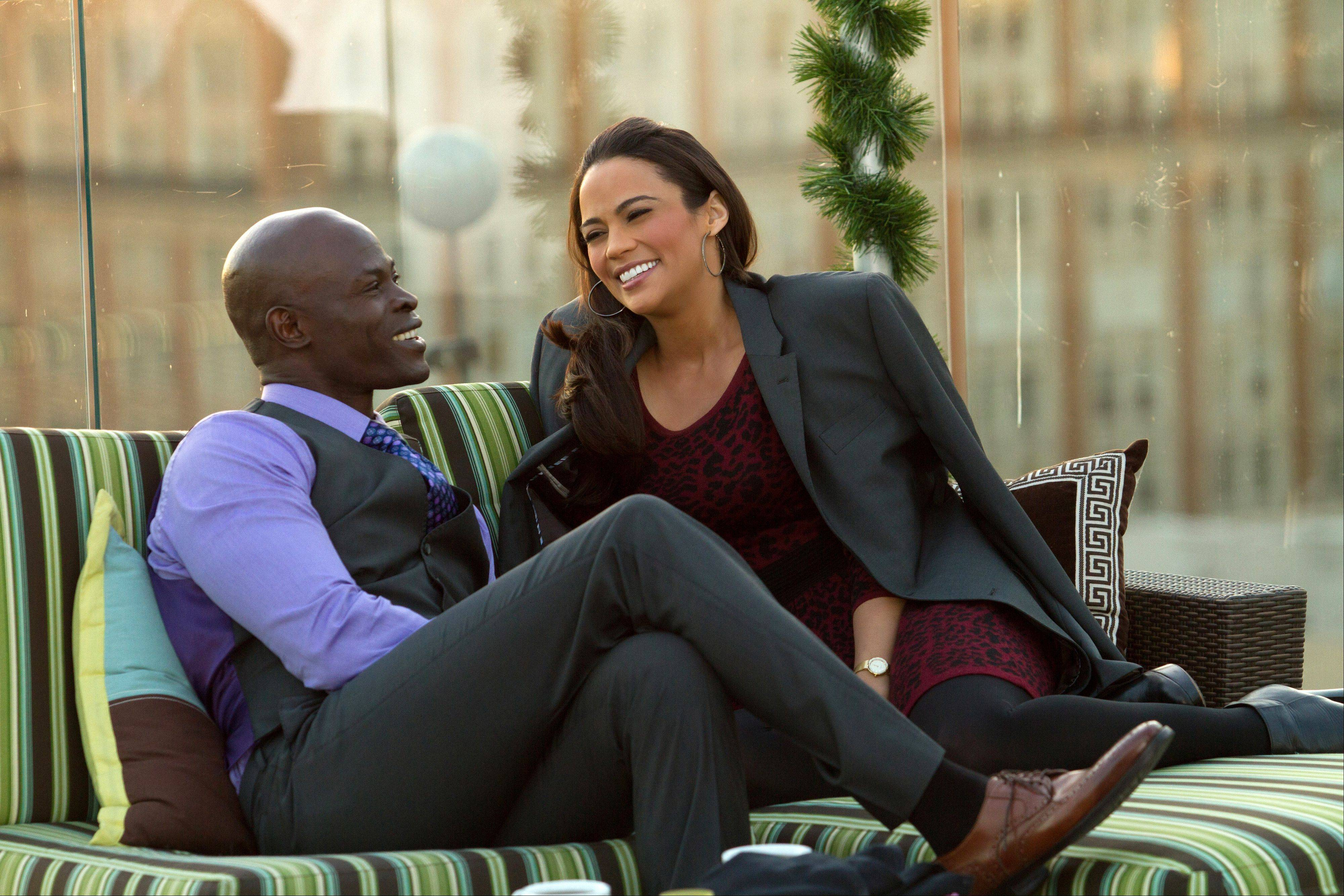 "A wealthy globe-trotter (Djimon Hounsou) tries to persuade a flight attendant (Paula Patton) to fly away with him in ""Baggage Claim."""