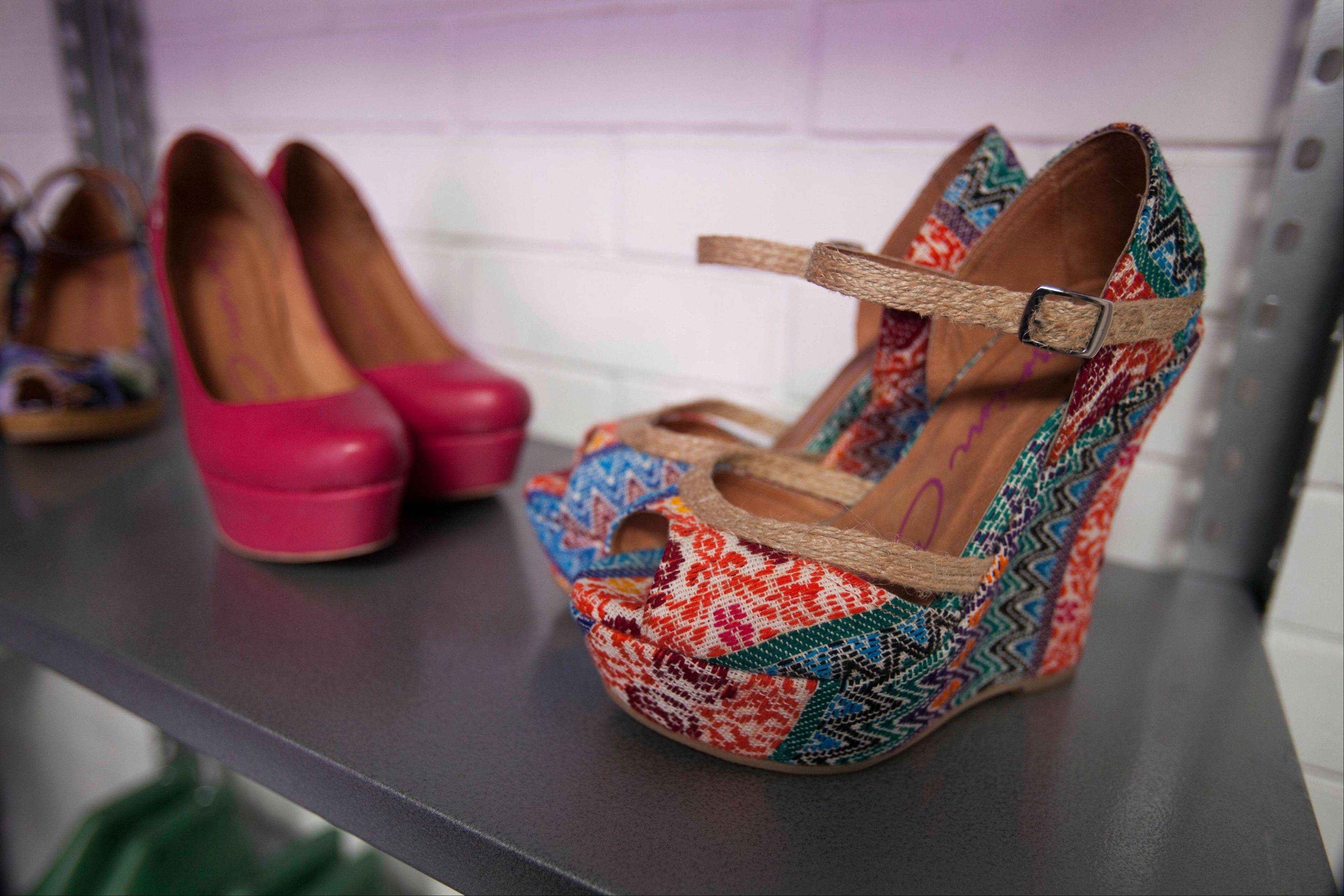 A pair of wedges show toes designed by Karim Corzo with embroidered Guatemalan fabric sit on a shelf at a factory where the shoes are handmade in Guatemala City.