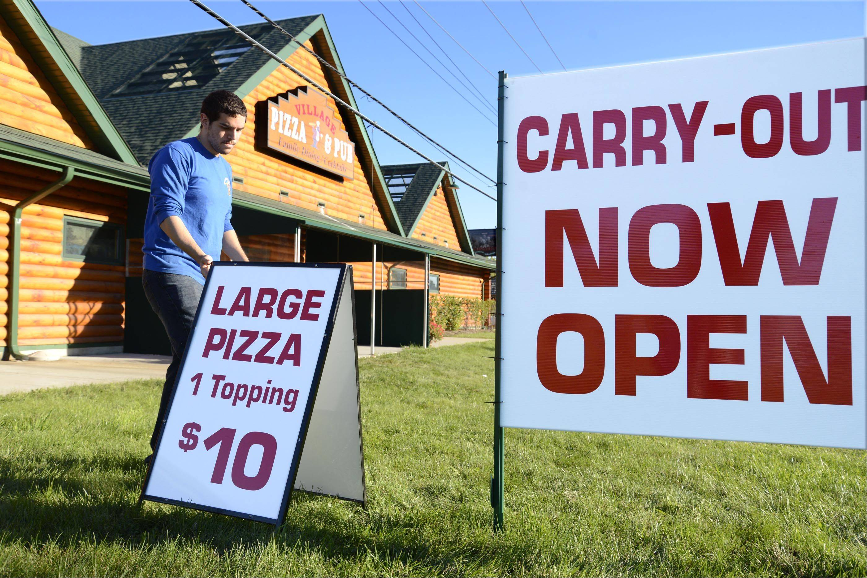 Michael Morino lets people know a portion of Village Pizza & Pub in Carpentersville has reopened.