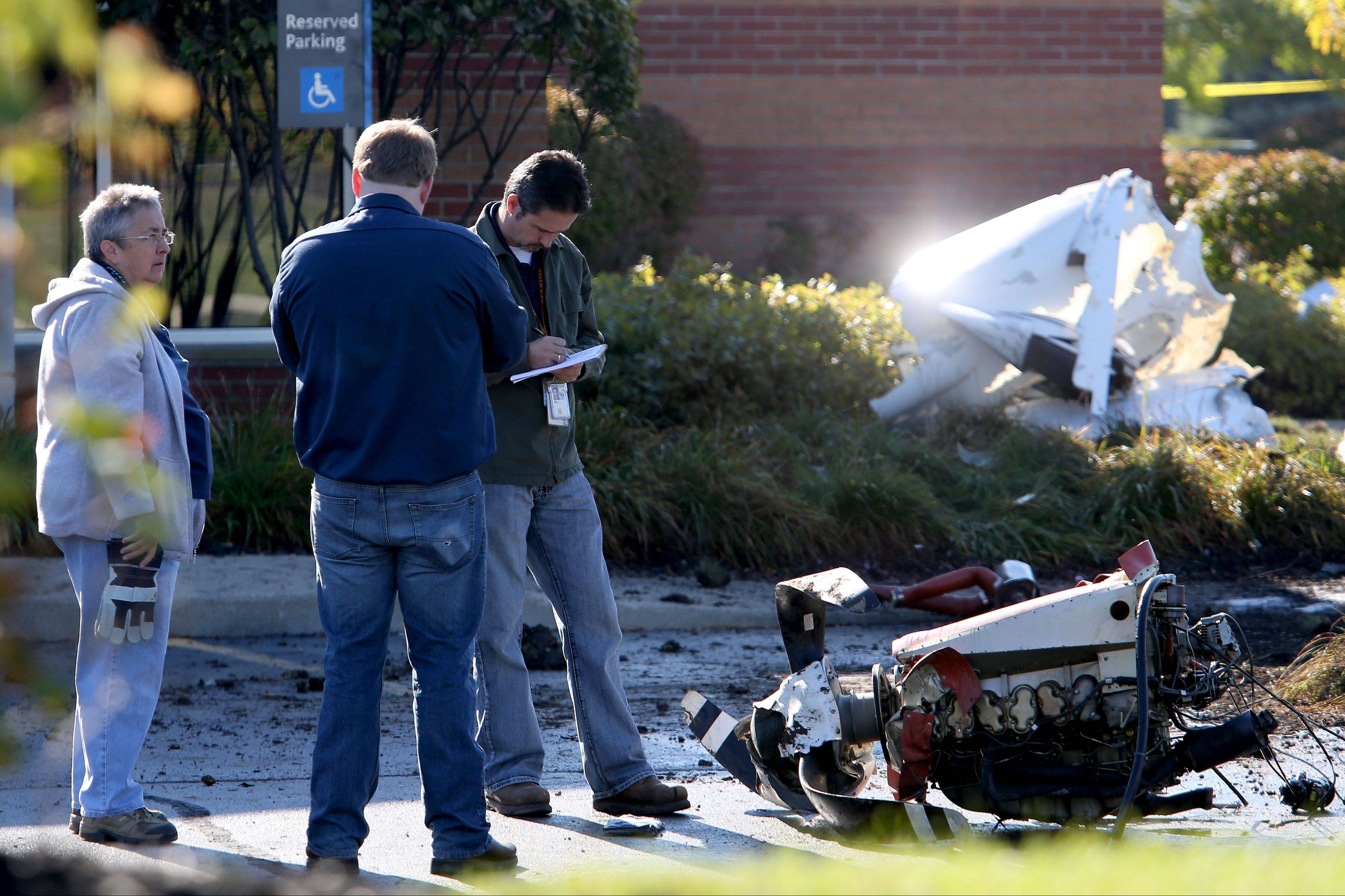 FAA investigators on Thursday look over the wreckage of a small plane that crashed in Bolingbrook, killing a doctor and his wife from Kentucky.