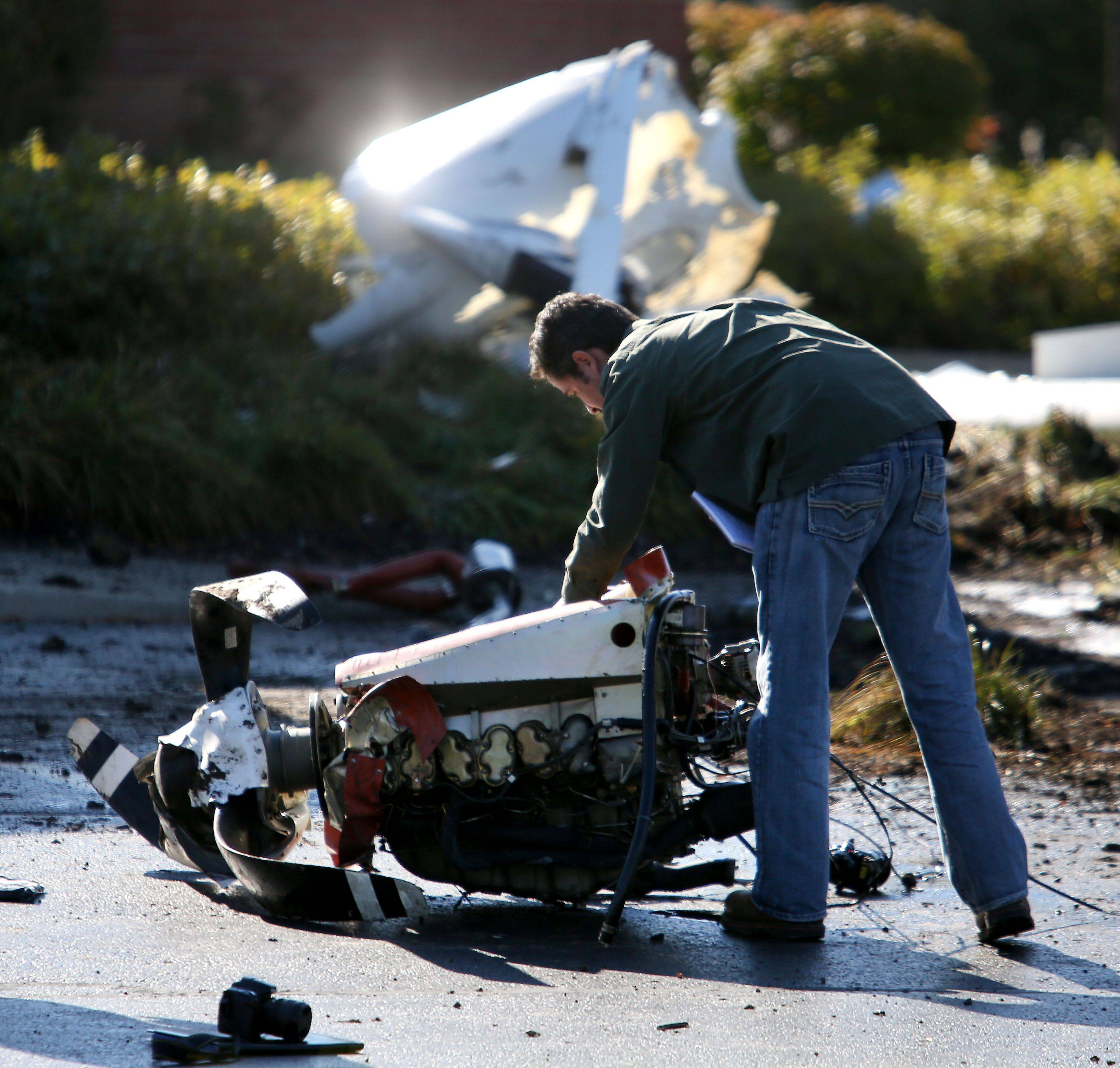 Investigators from the FAA on Thursday look over the wreckage of a plane crash that claimed two lives in Bolingbrook.