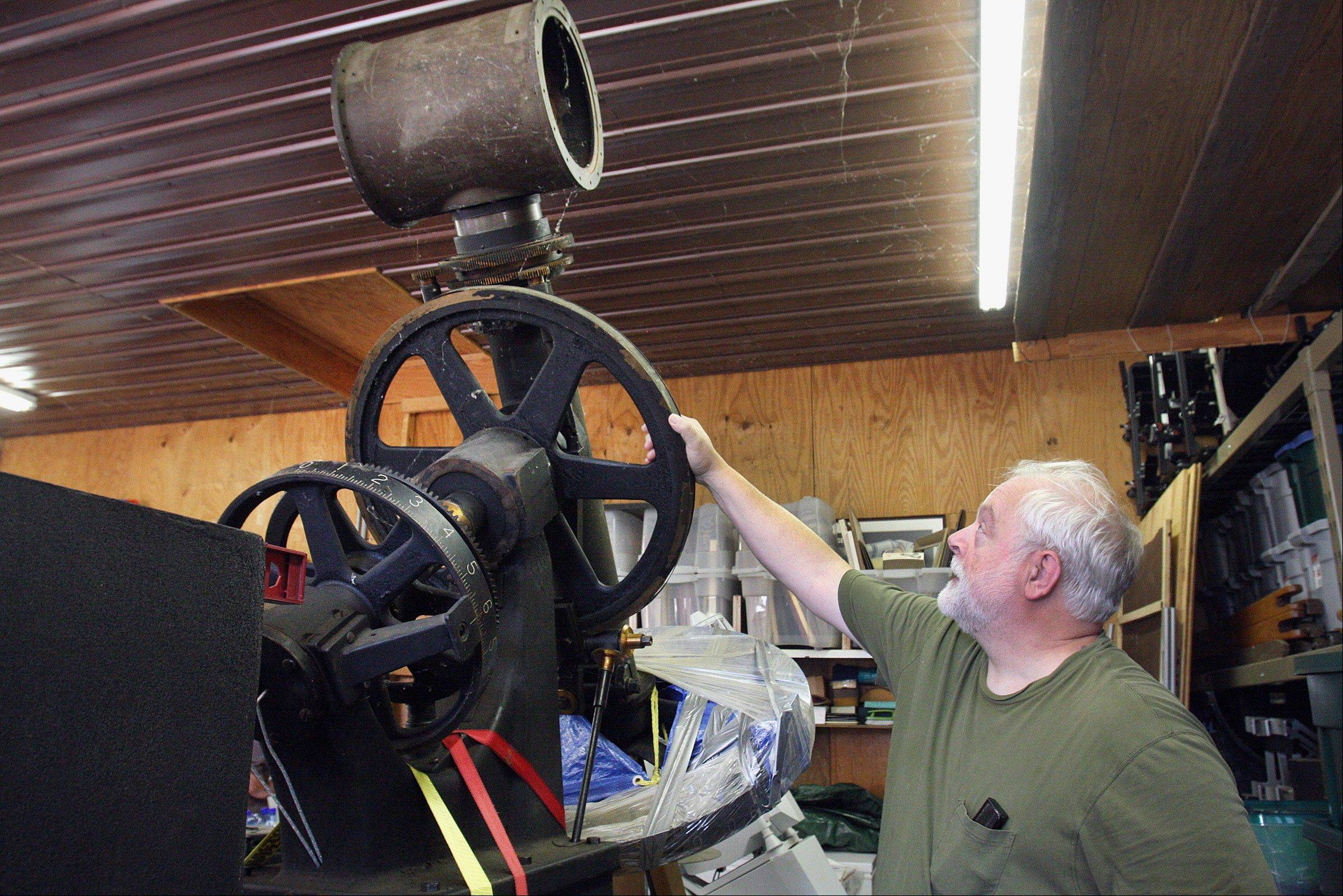 Telescope collector John Allseits inspects part of the wheel of his 1950 German equatorial refractor telescope housed in a building at his farm.