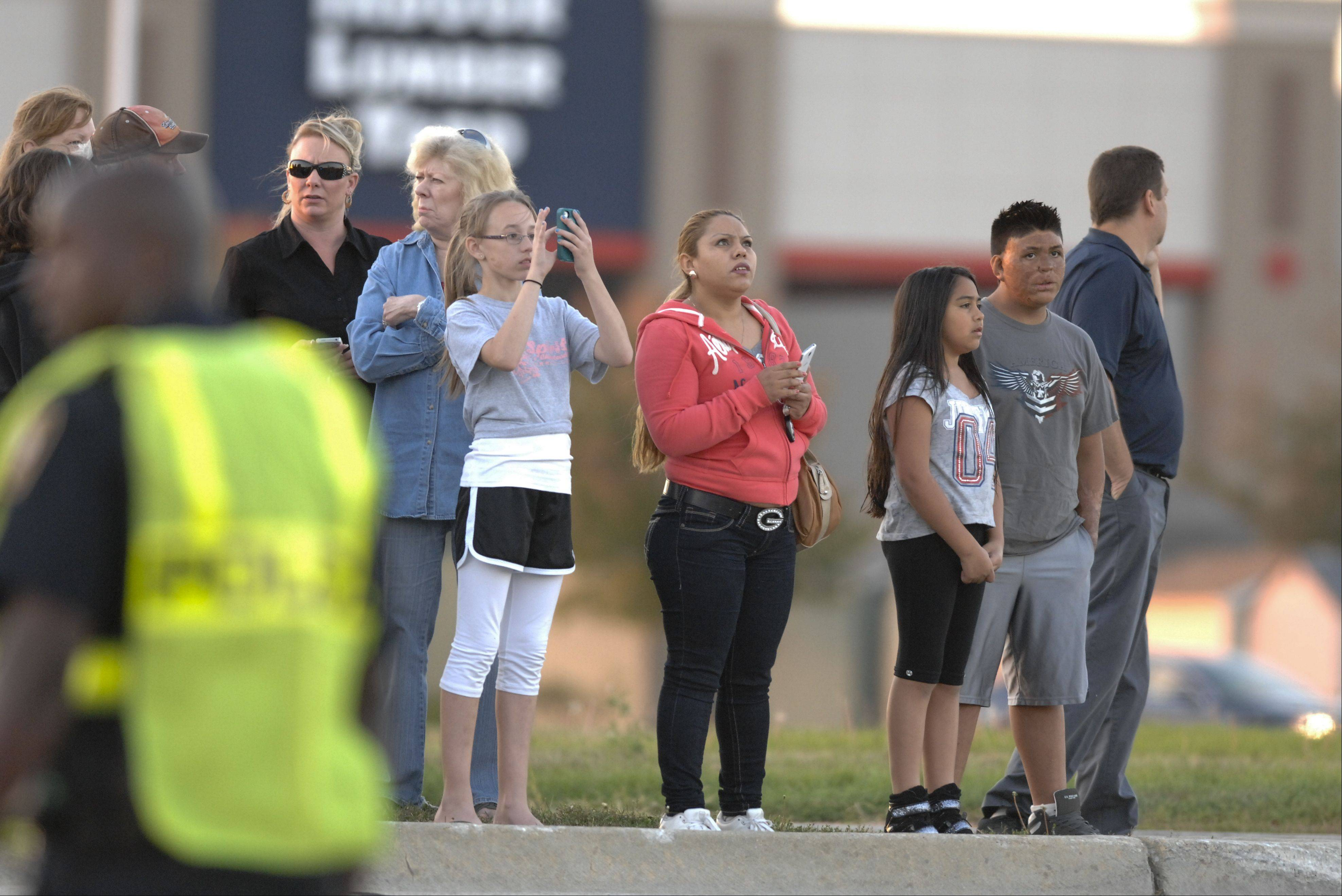 Onlookers take photos and watch as investigators examine the site of a plane crash in the parking lot of a Chase bank on Weber Road near the Clow International Airport in Bolingbrook on Wednesday.