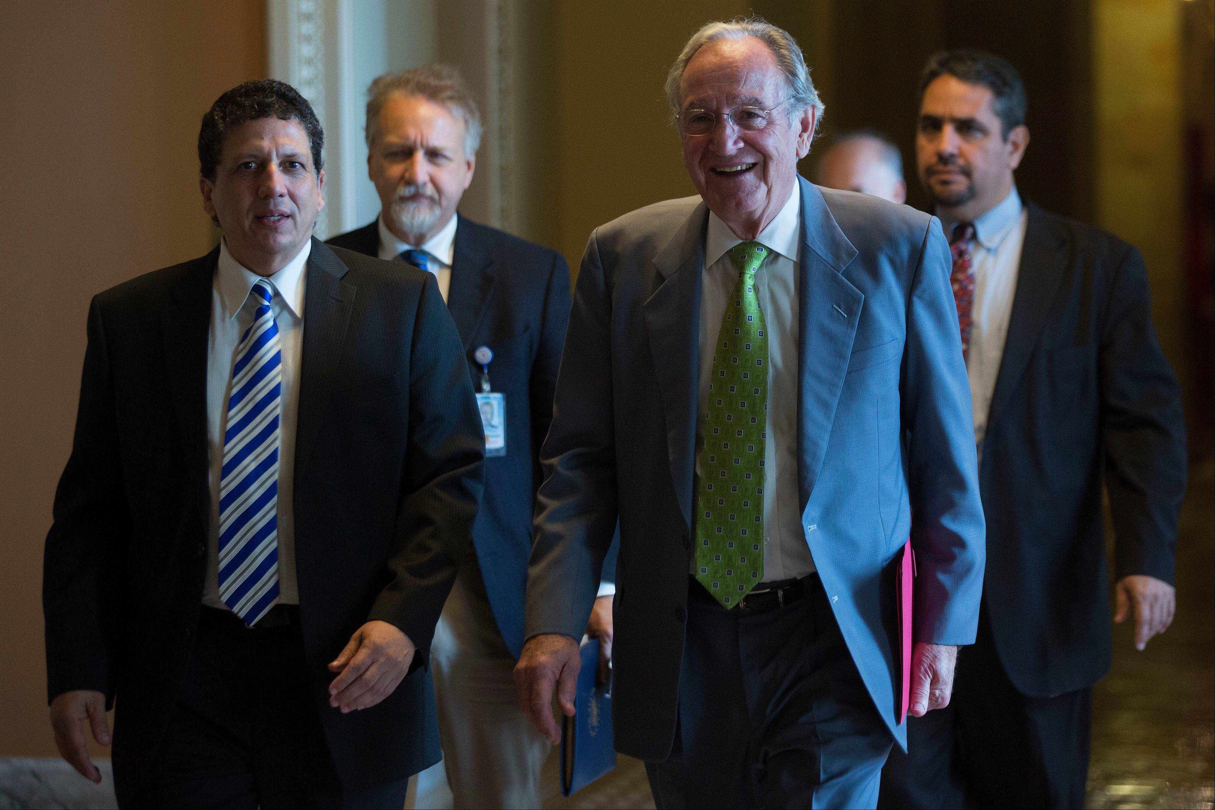 Senator Tom Harkin, a Democrat from Iowa, second from right, walks Friday in the U.S. Capitol in Washington, D.C. The U.S. Senate voted to finance the government through Nov. 15 after removing language to choke off funding for the health care law, putting pressure on the House to avoid a federal shutdown set to start Oct. 1.