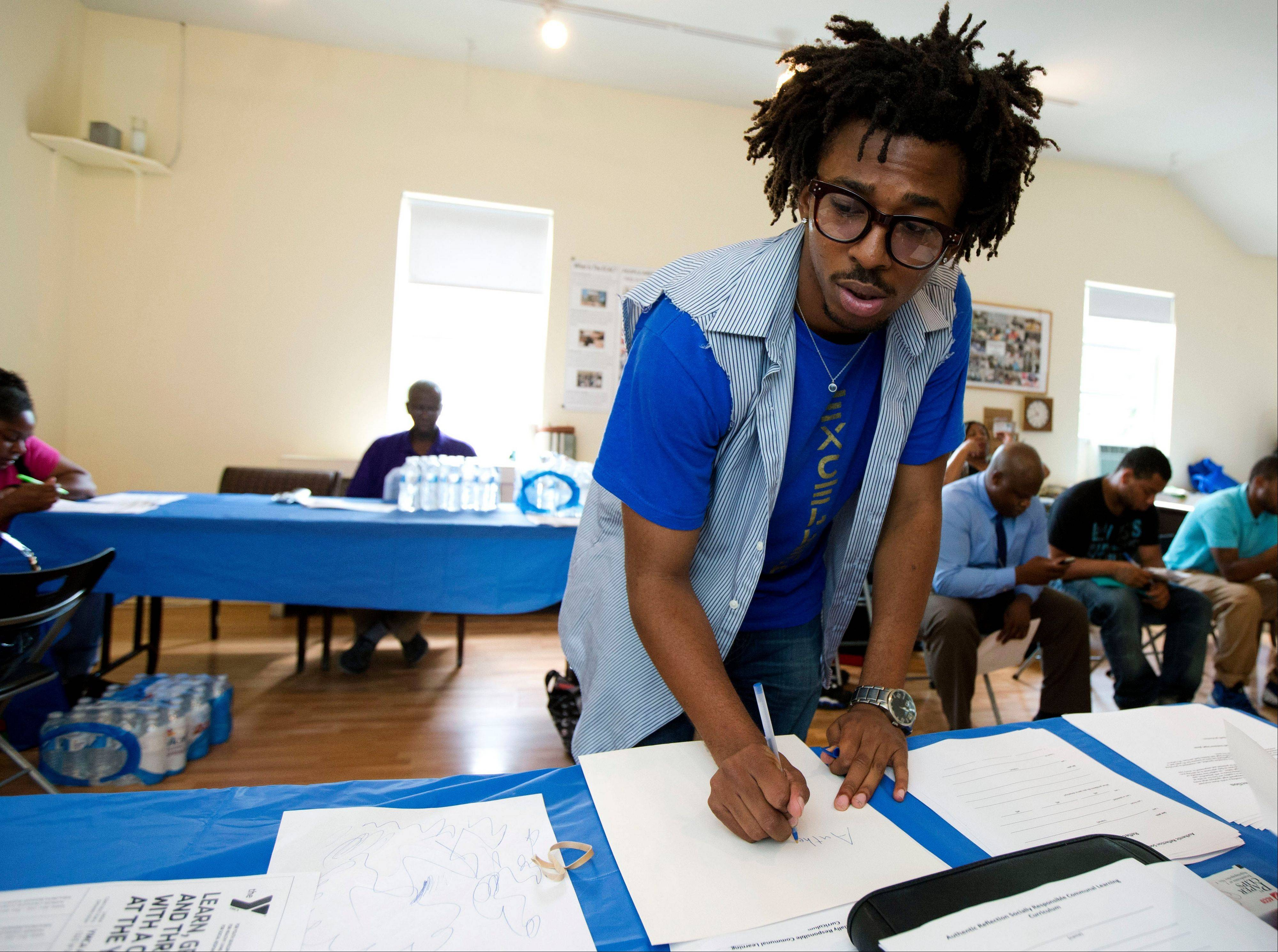 Americorps volunteer John Harris III, who is helping to coordinate a jobs fair program, fills up some documents for job seekers in Washington. The number of people seeking unemployment benefits has sunk to its lowest point in six years because few companies are laying anyone off anymore.