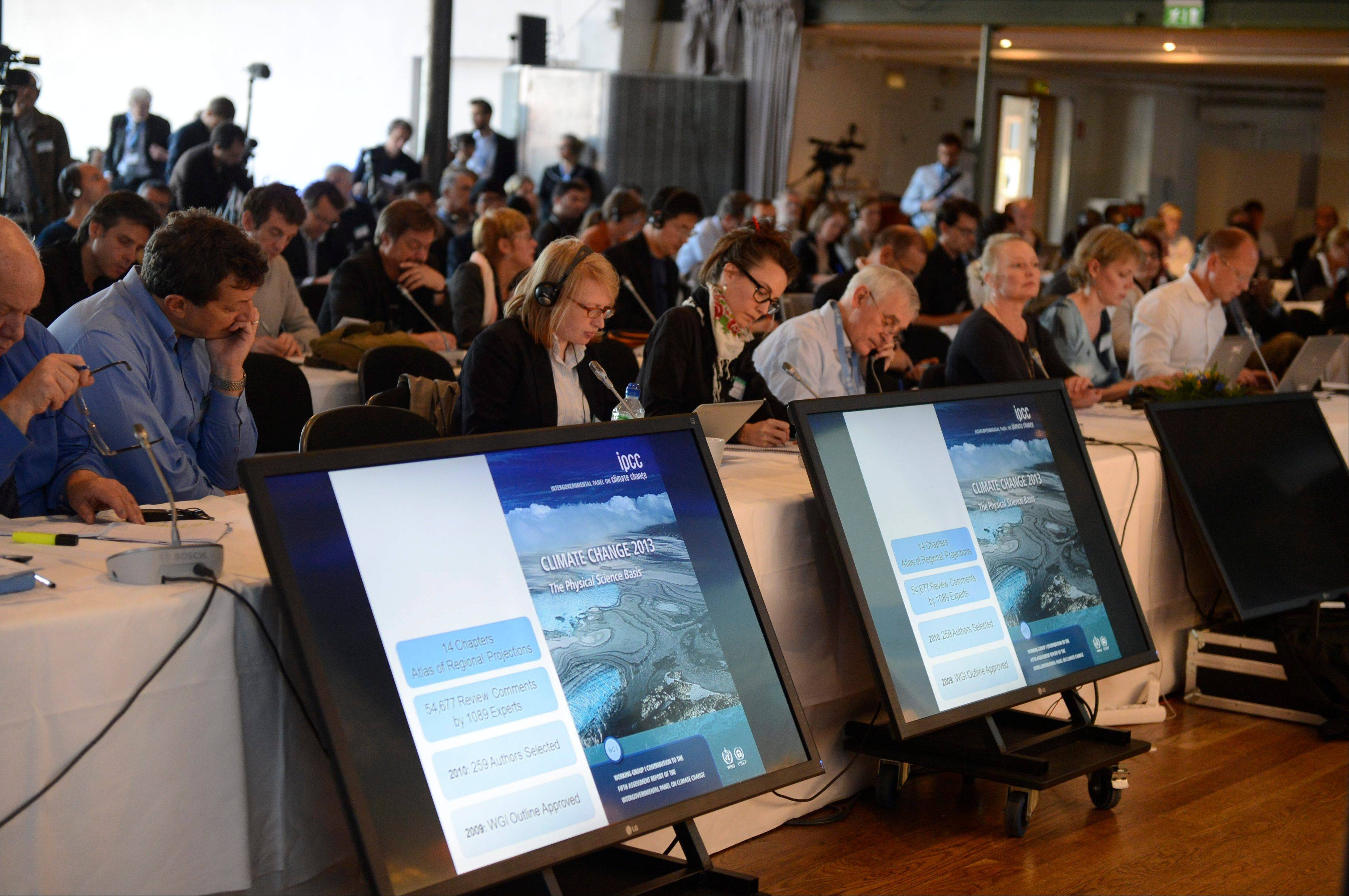 Media representatives follow the U.N. IPCC climate report presentation, in Stockholm, Friday.