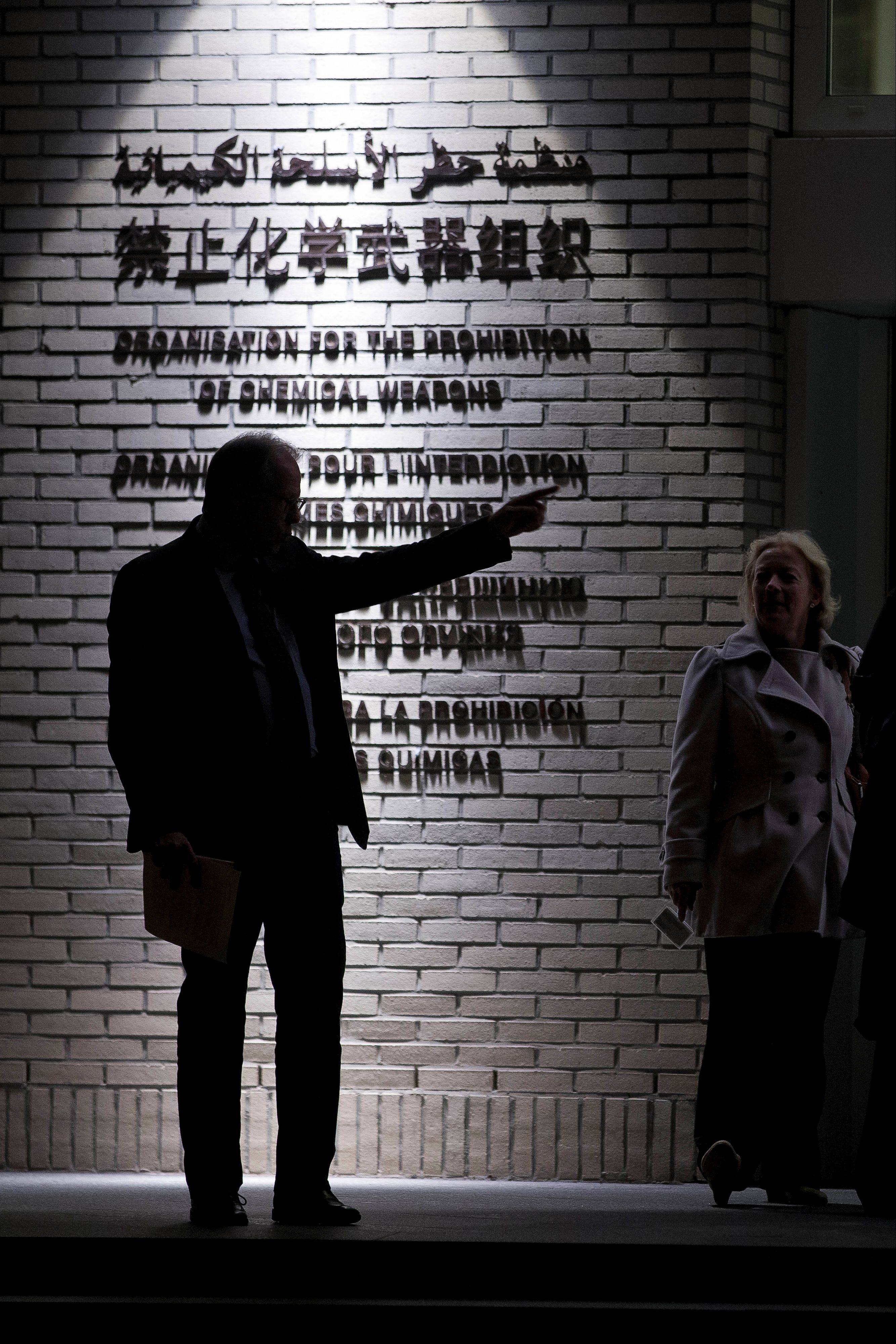 People talk Friday at the entrance to the headquarters of the Organization for the Prohibition of Chemical Weapons, OPCW, in The Hague, Netherlands.