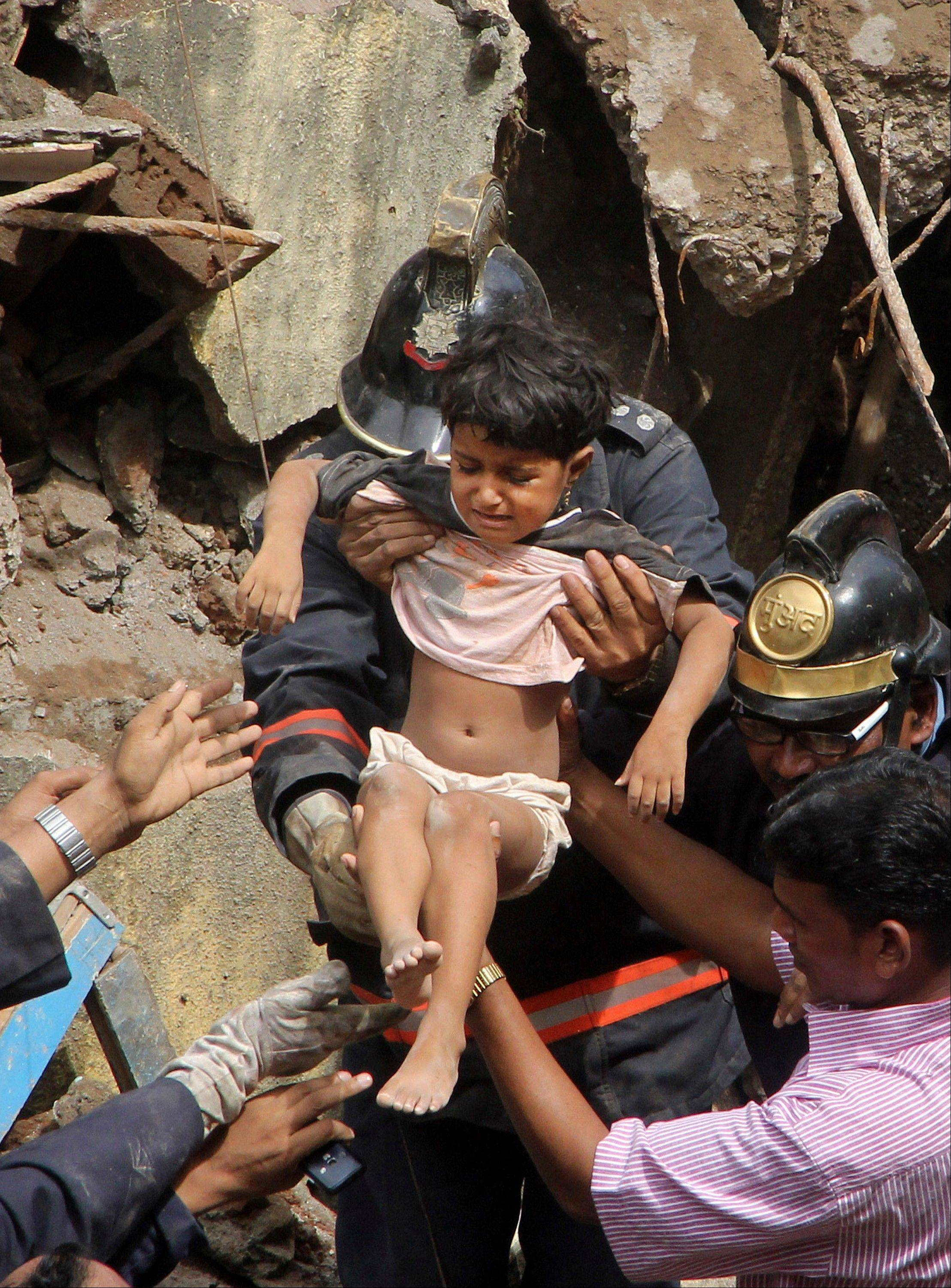Indian Fire officials rescue a girl from the debris of a collapsed building in Mumbai, India, Friday, Sept. 27, 2013. The multistory residential building collapsed in India�s financial capital of Mumbai early Friday.