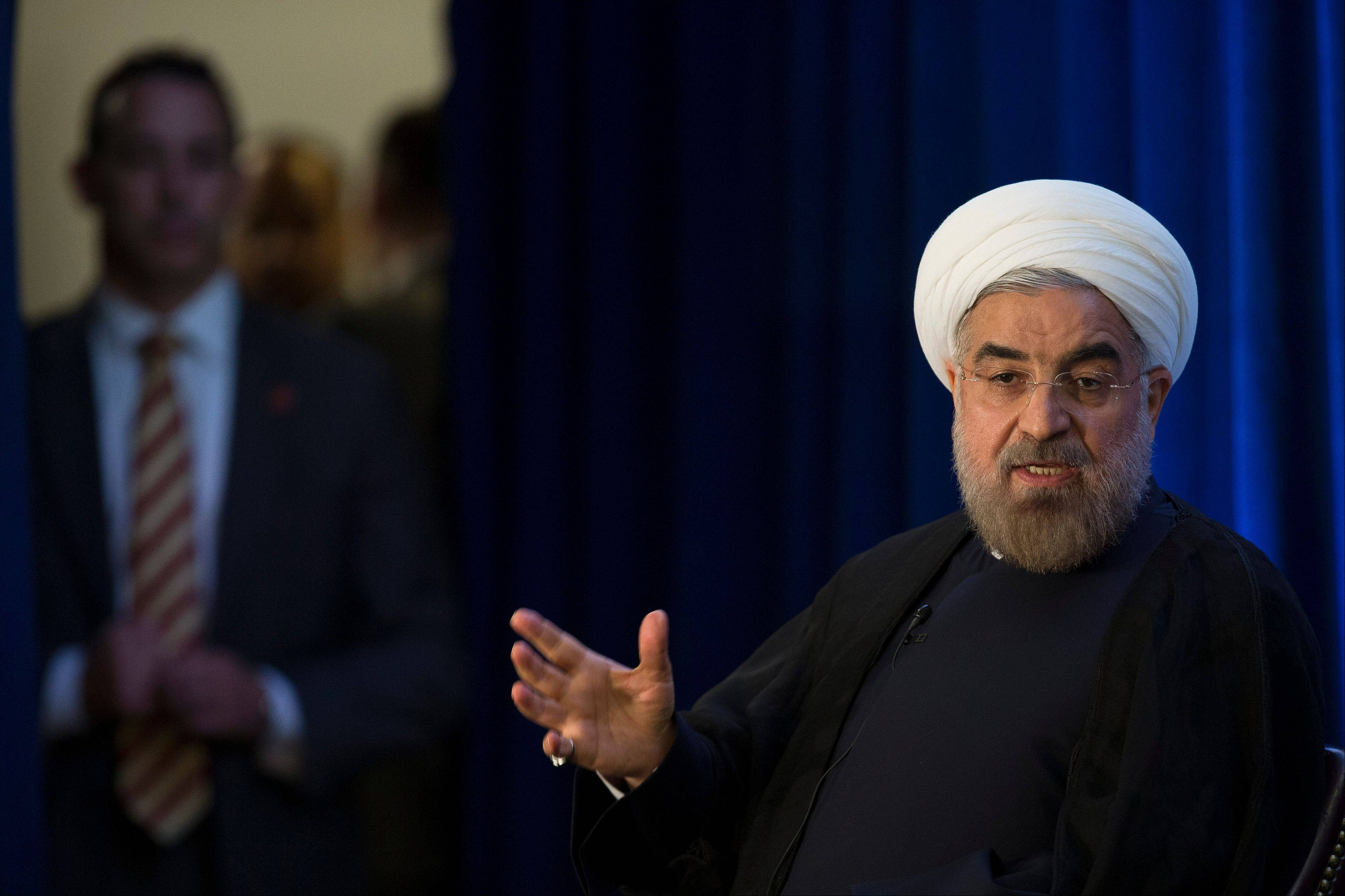 Iranian President Hassan Rouhani listens to a question as security personnel waits in the wings during an address and discussion hosted by the Asia Society and the Council on Foreign Relations at the Hilton Hotel in midtown Manhattan, Thursday, Sept. 26, 2013, in New York.