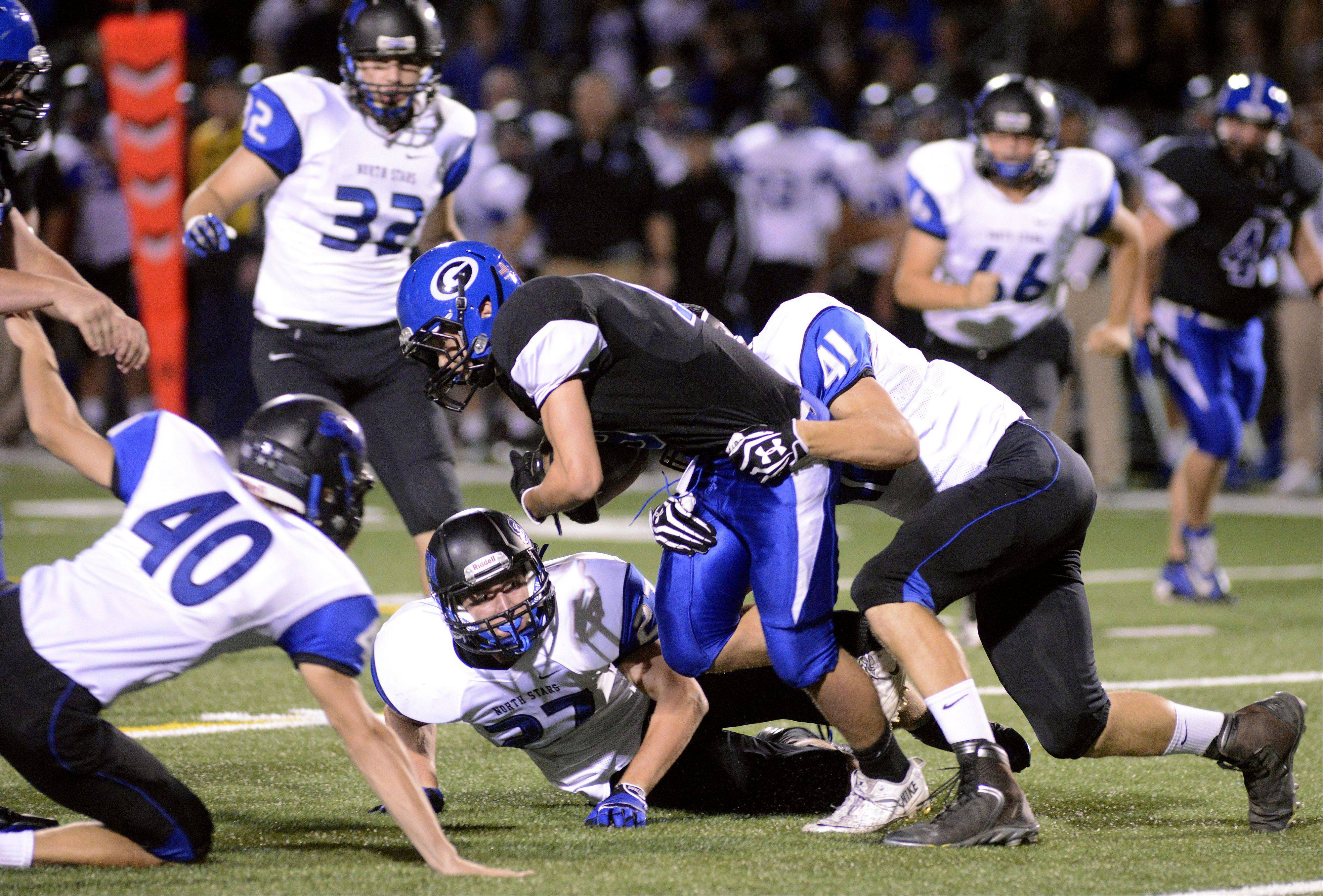 St. Charles North�s Jordan Bergren (41) takes down Geneva�s Chris Barger while teammates Nick Davison (40) and Mitchell Riggs (27) slide in to help in the first quarter on Friday.