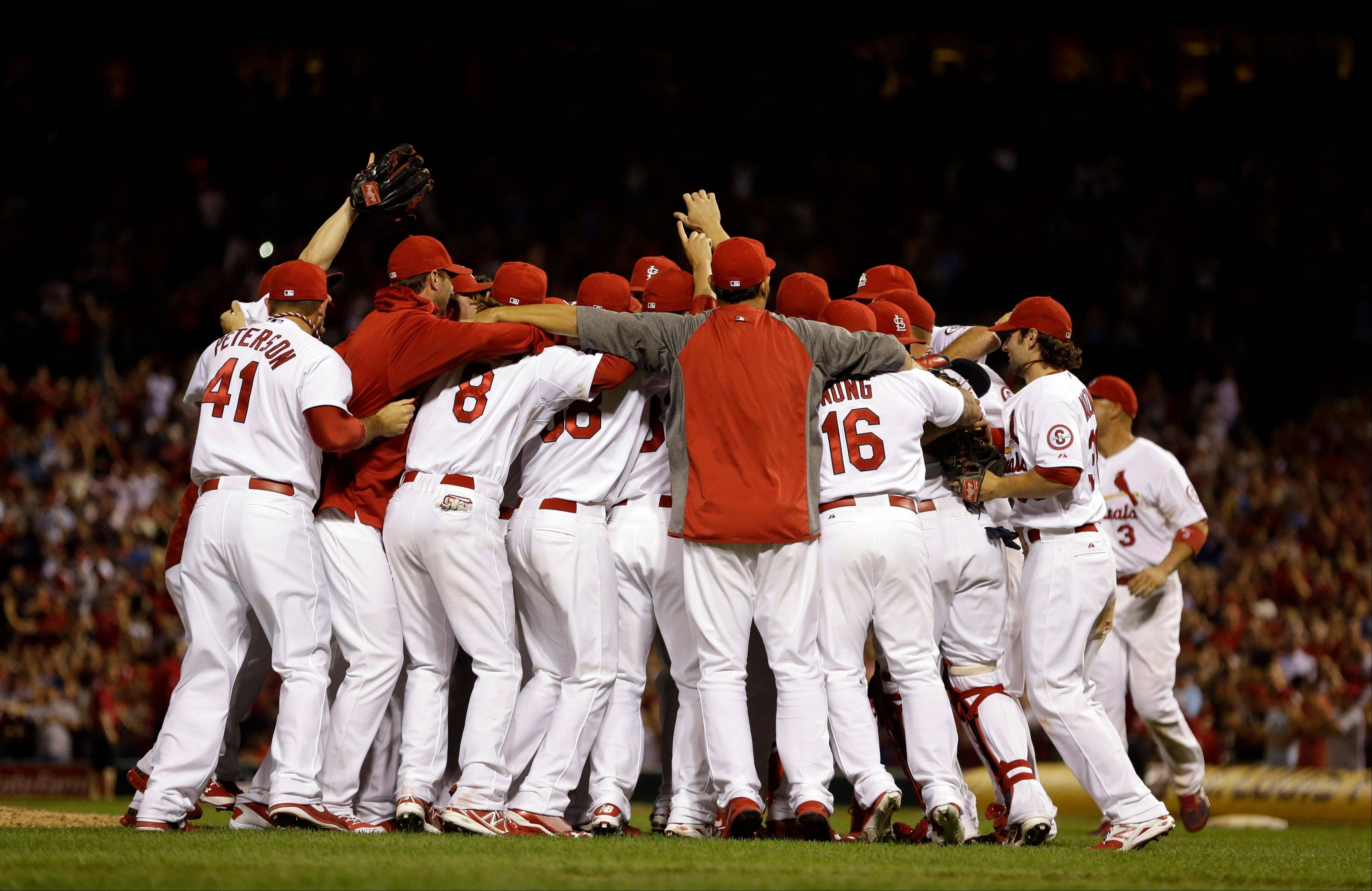Members of the St. Louis Cardinals celebrate after beating the Chicago Cubs Friday night at home to clinch the NL Central title.