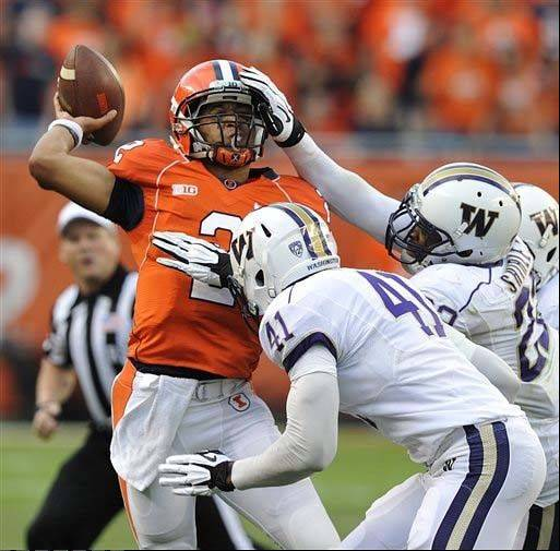 Illinois� Nathan Scheelhaase tries to throw under pressure from Washington�s Travis Feeney (41) and Josh Shirley during the first half the Sept. 14 game in Chicago. Illinois is averaging 37 points a game, but in three games the Illini have only reached the red zone 11 times.