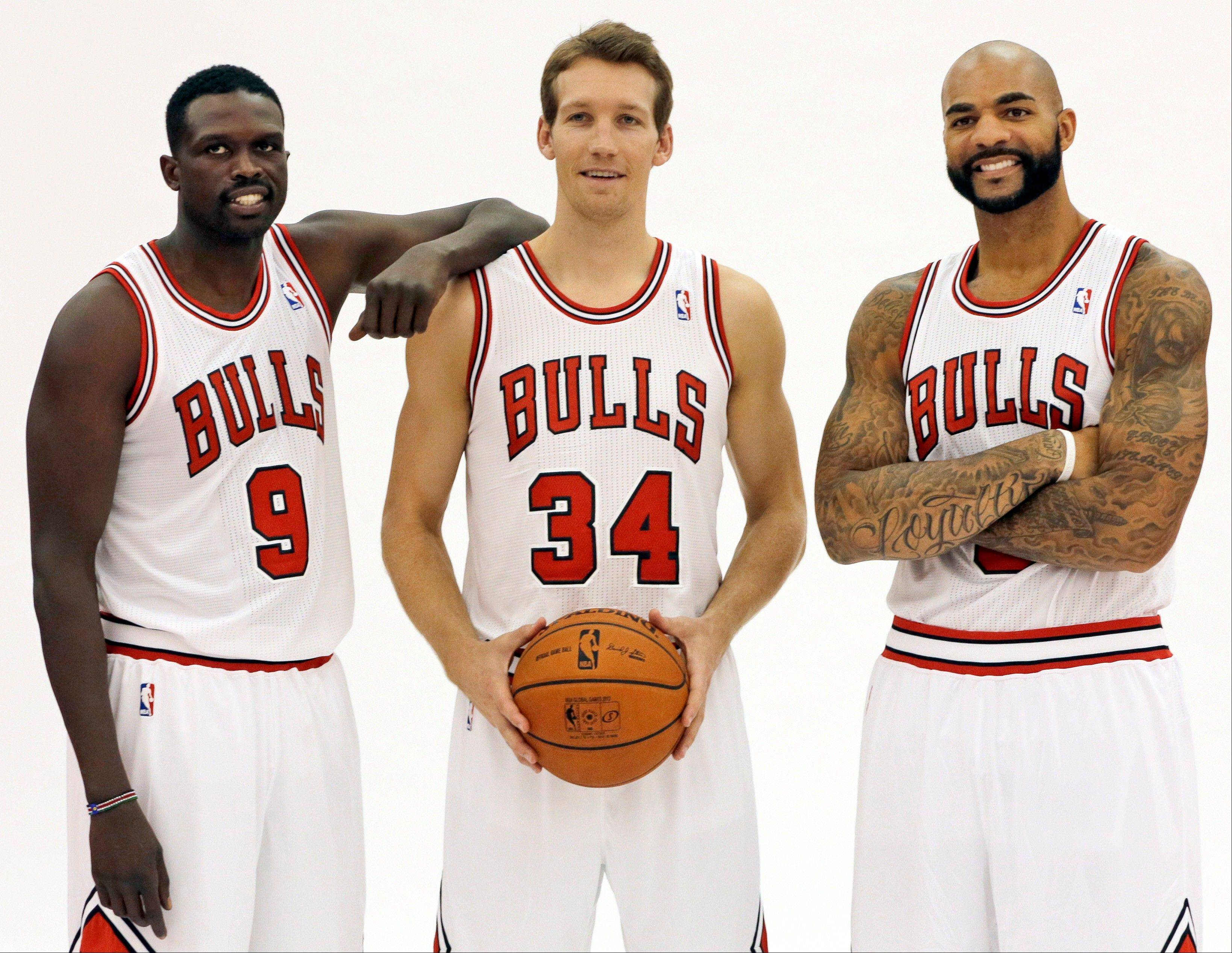 Forward Luol Deng, left, wouldn�t talk about his Bulls contract situation on Friday, but he did take time to take photos with Mike Dunleavy and Carlos Boozer, right, at the Berto Center.