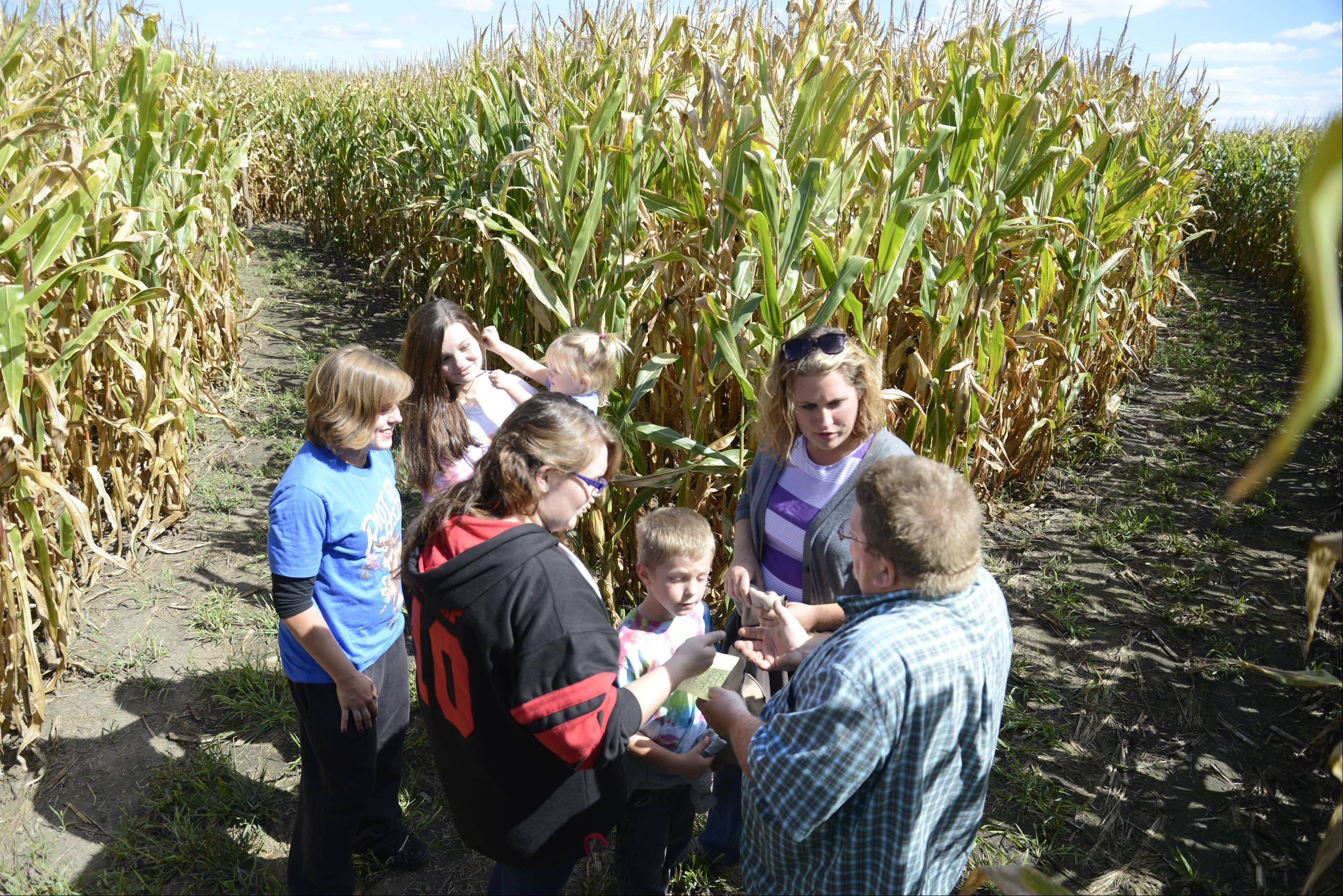 Owner Ben Norton gives directions to Jessica, Brody, Kelsey and Lexi Hanson, of St. Charles, and Hayle and Katy Pillsburg, of Maple Park, at the Norton's Produce & Garden Center corn maze in St. Charles.