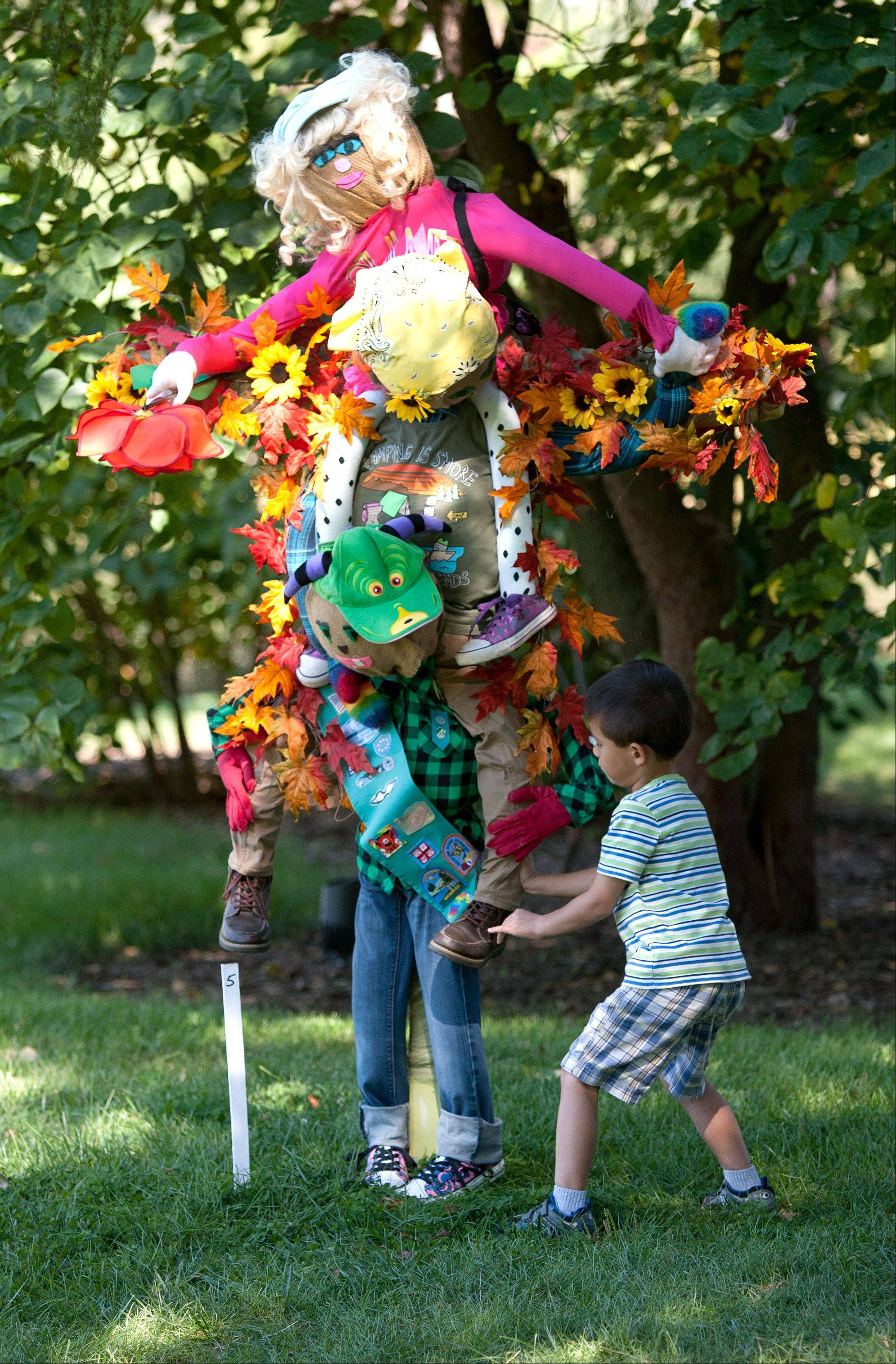 "Theo Marchand, 5, of Naperville, examines a scarecrow called ""Together We Can Do Anything"" by Scouts from Hammerschmidt Elementary School in Lombard."