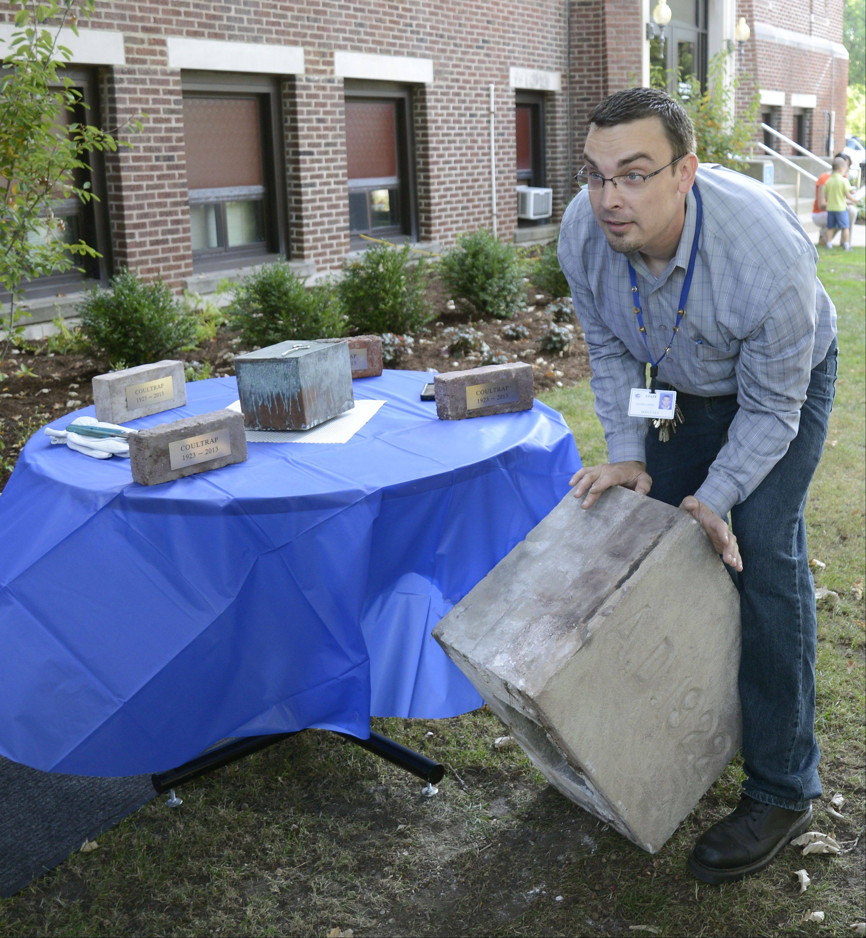 Scott Ney, a part of the Coultrap Educational Services Center administration, tips over the marker stone from the recently razed Coultrap Elementary School to show where the time capsule was stored.