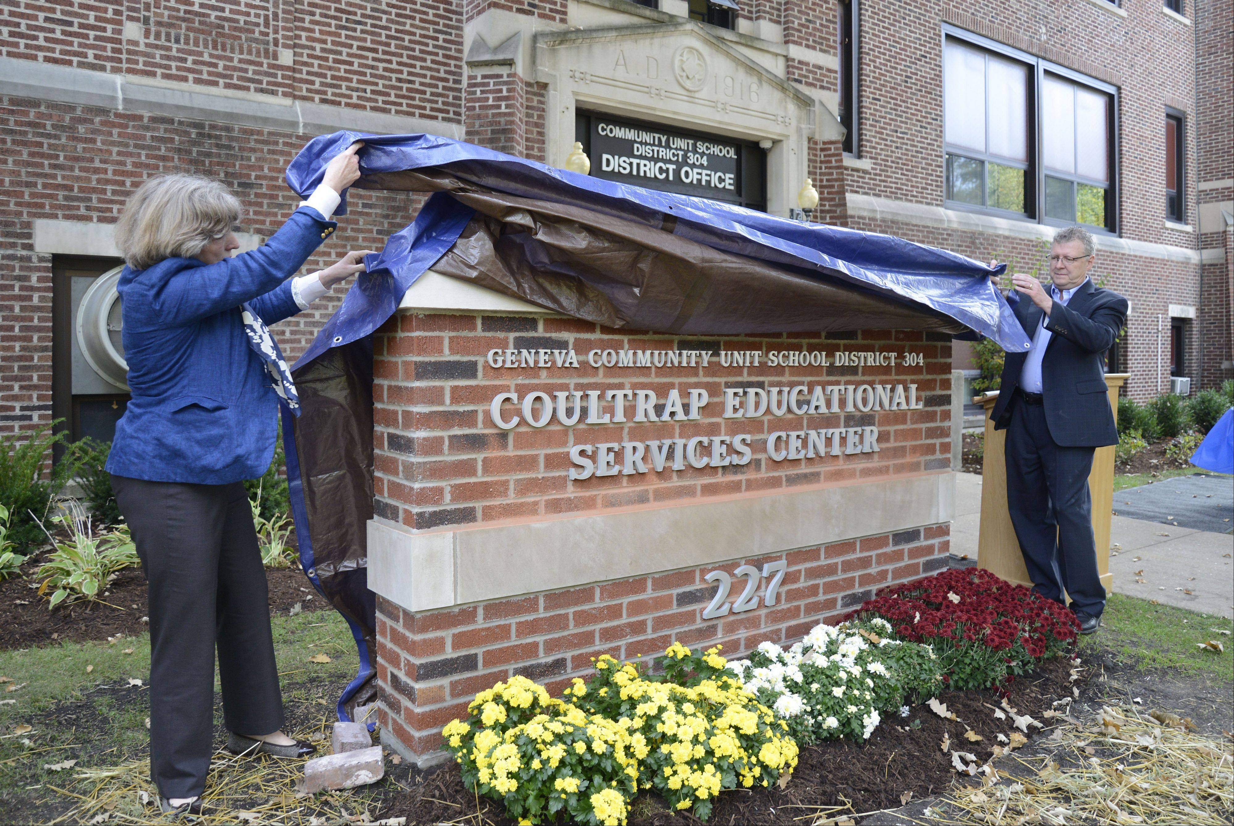 Martha Coultrap of New York City and her brother Paul Coultrap of Downers Grove unveil the sign for the Coultrap Educational Services Center named in honor of their grandfather Harry M. Coultrap on Saturday. Bricks from the recently razed Coultrap Elementary School were used to make the sign, as well as a brick walkway to the adjacent flagpole.