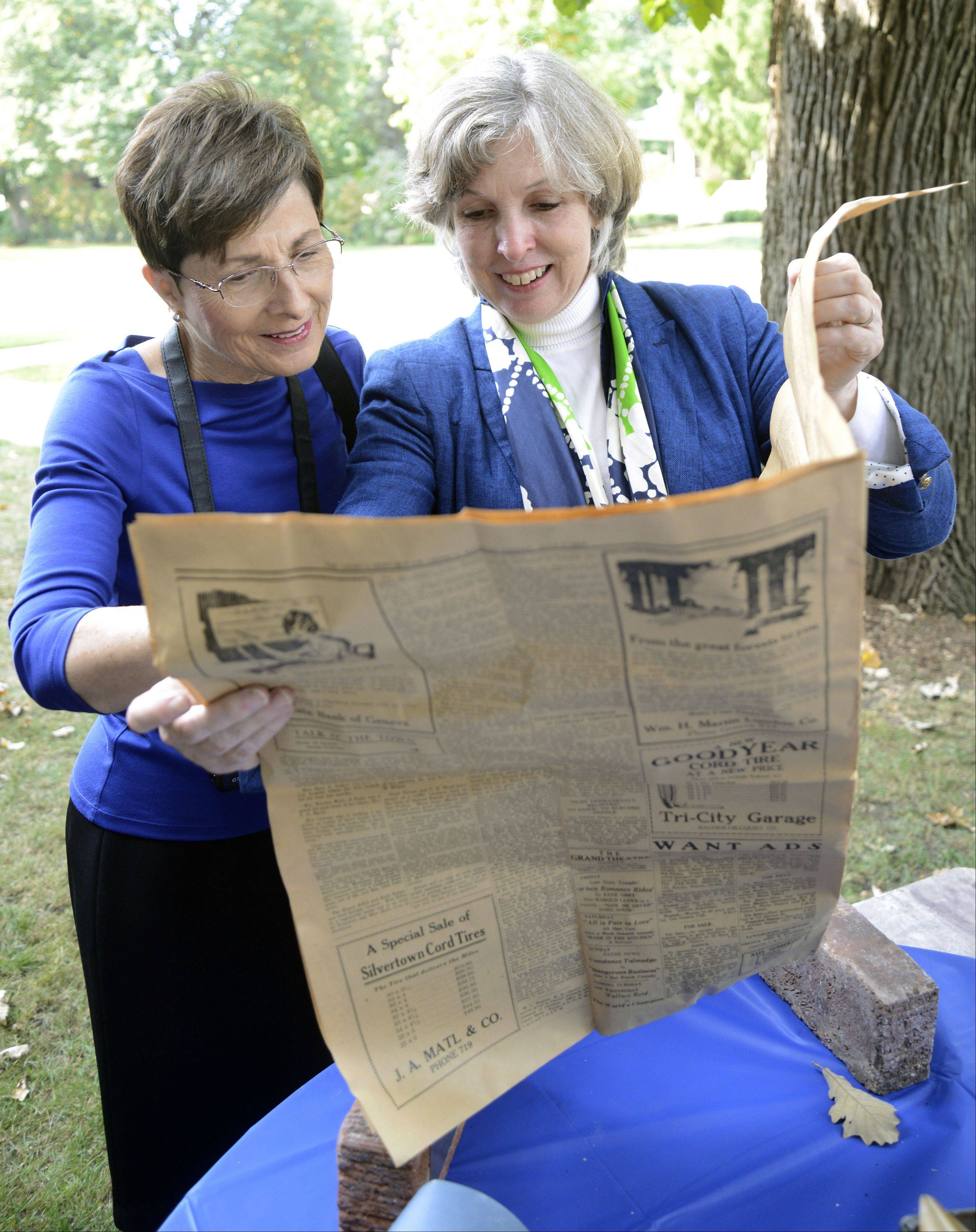 Ellen Frech of Palatine, left, and Martha Coultrap, read a commentary piece about flappers in the newspaper dated Aug. 11, 1922, after it was removed from a time capsule inside a marker stone of the recently razed Coultrap Elementary School in Geneva.