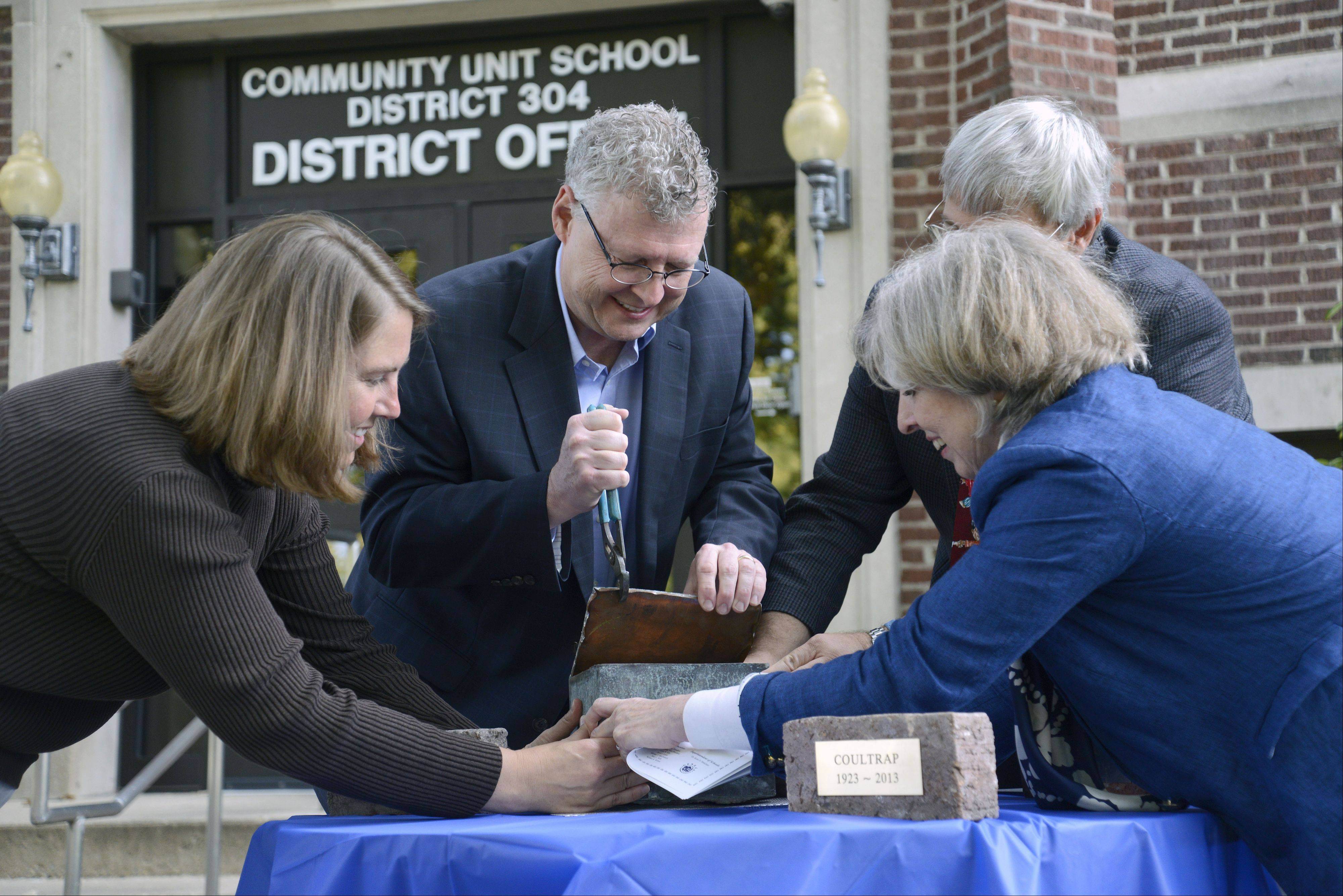 Paul Coultrap, center, of Downers Grove pries open a time capsule from 1922 with the help of Board of Education Vice President Kelly Nowak, left, Superintendent Kurt Mutchler, and Martha Coultrap of New York City. Inside the time capsule was a 1922 high school yearbook, a copy of a newspaper dated Aug. 11, 1922, a few silver coins and the school district's resolution.
