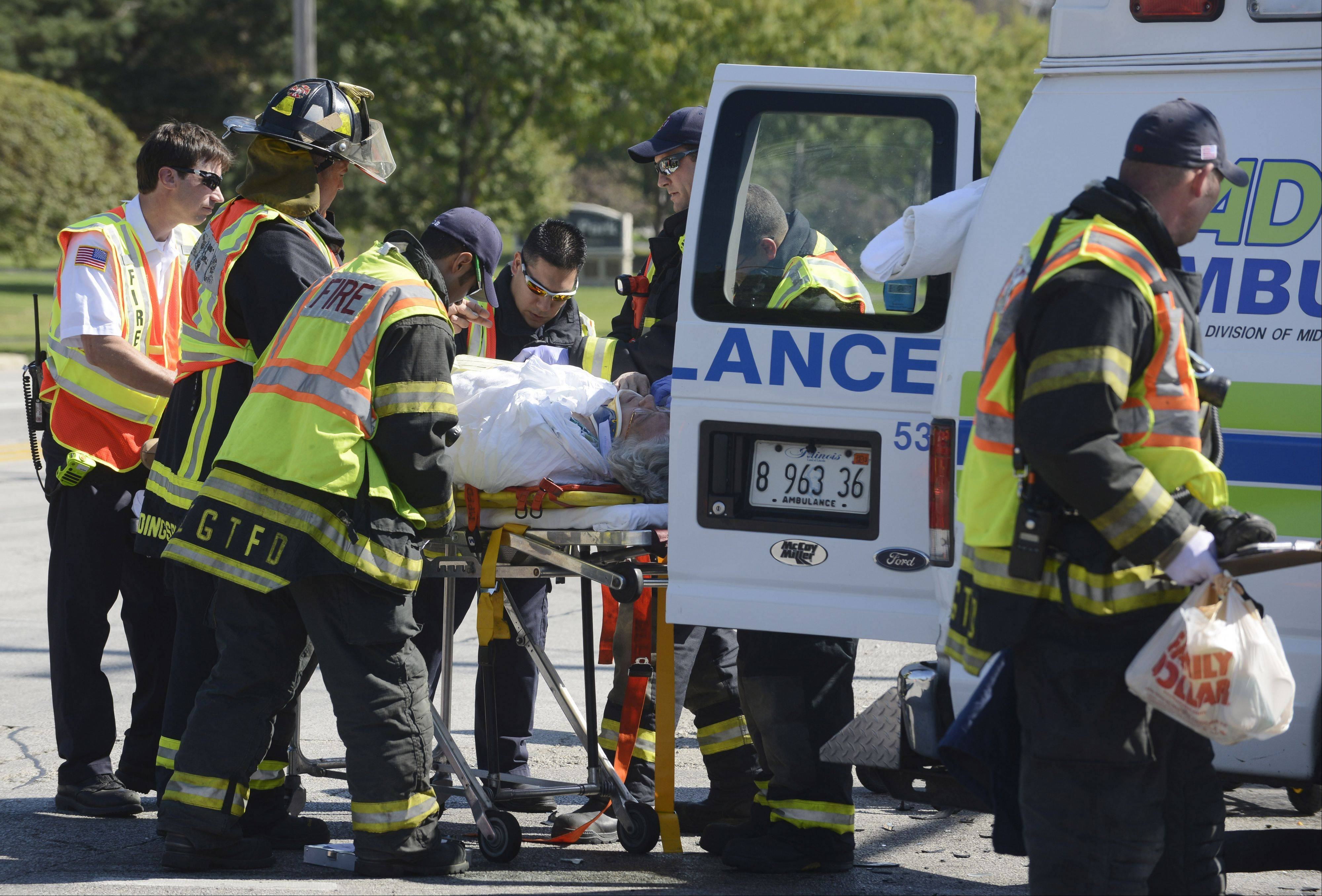 Mount Prospect paramedics transport a victim injured Friday morning in a three-vehicle crash that involved a private ambulance, SUV and an Elk Grove Township Senior Services bus.