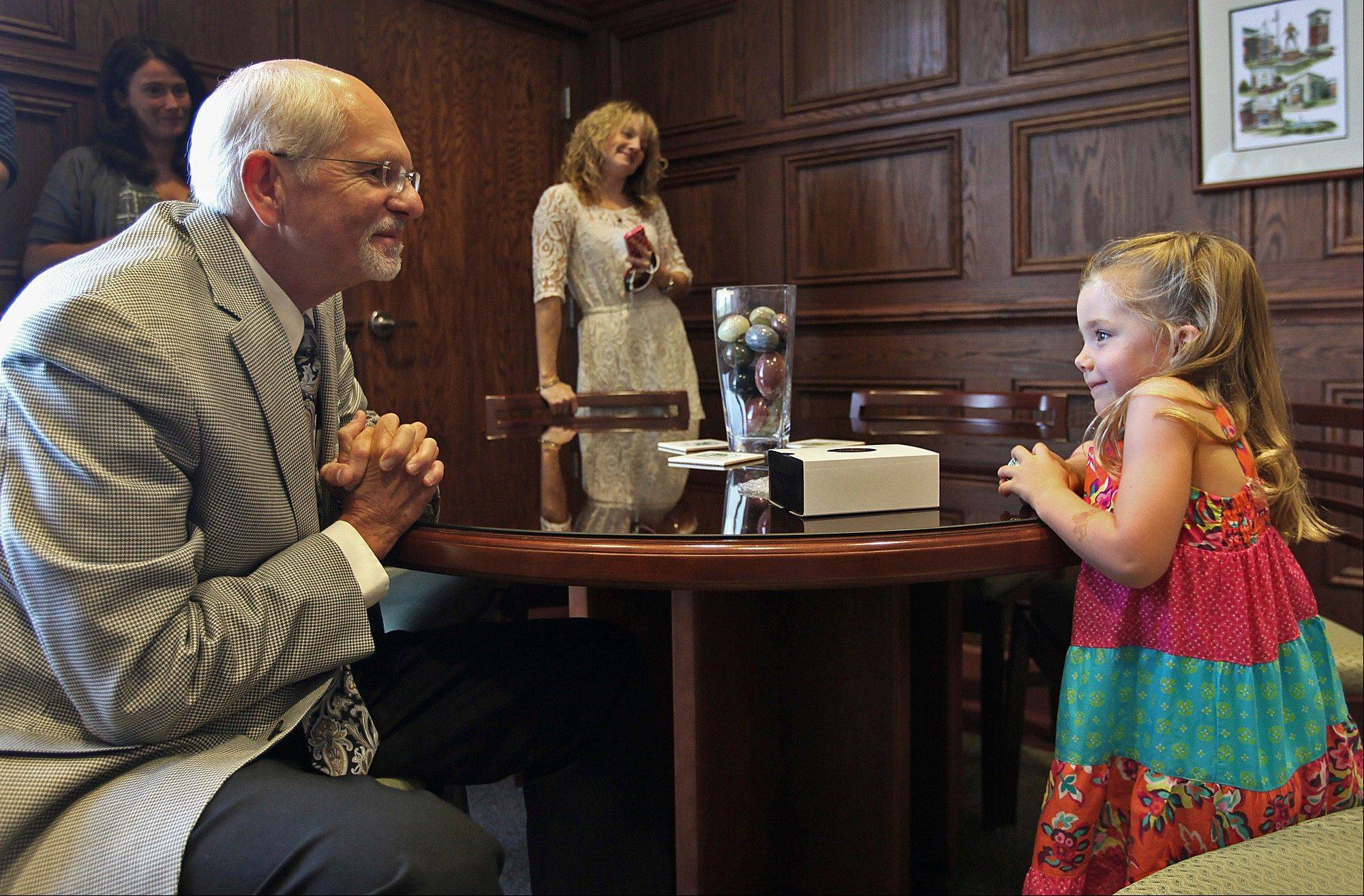 Associated Press John Wood Community College President John Letts, left, visits with 4-year-old Alexa Mosley in his office at the college in Quincy. Alexa recently told her parents that she wanted to visit big colleges to decide where to go to school in the future, so Letts and staff scheduled the campus tour.