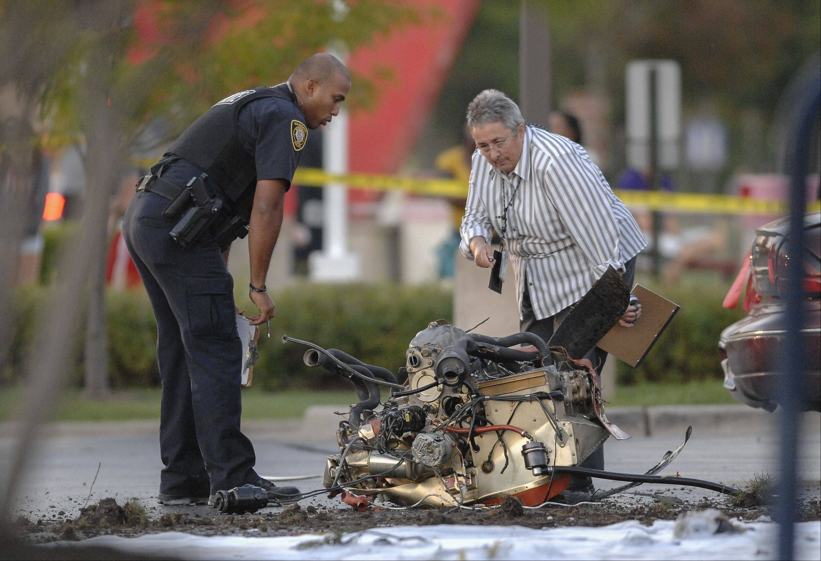 Investigators examine the site of a plane crash Wednesday afternoon in the parking lot of a Chase bank on Weber Road near Clow International Airport in Bolingbrook.