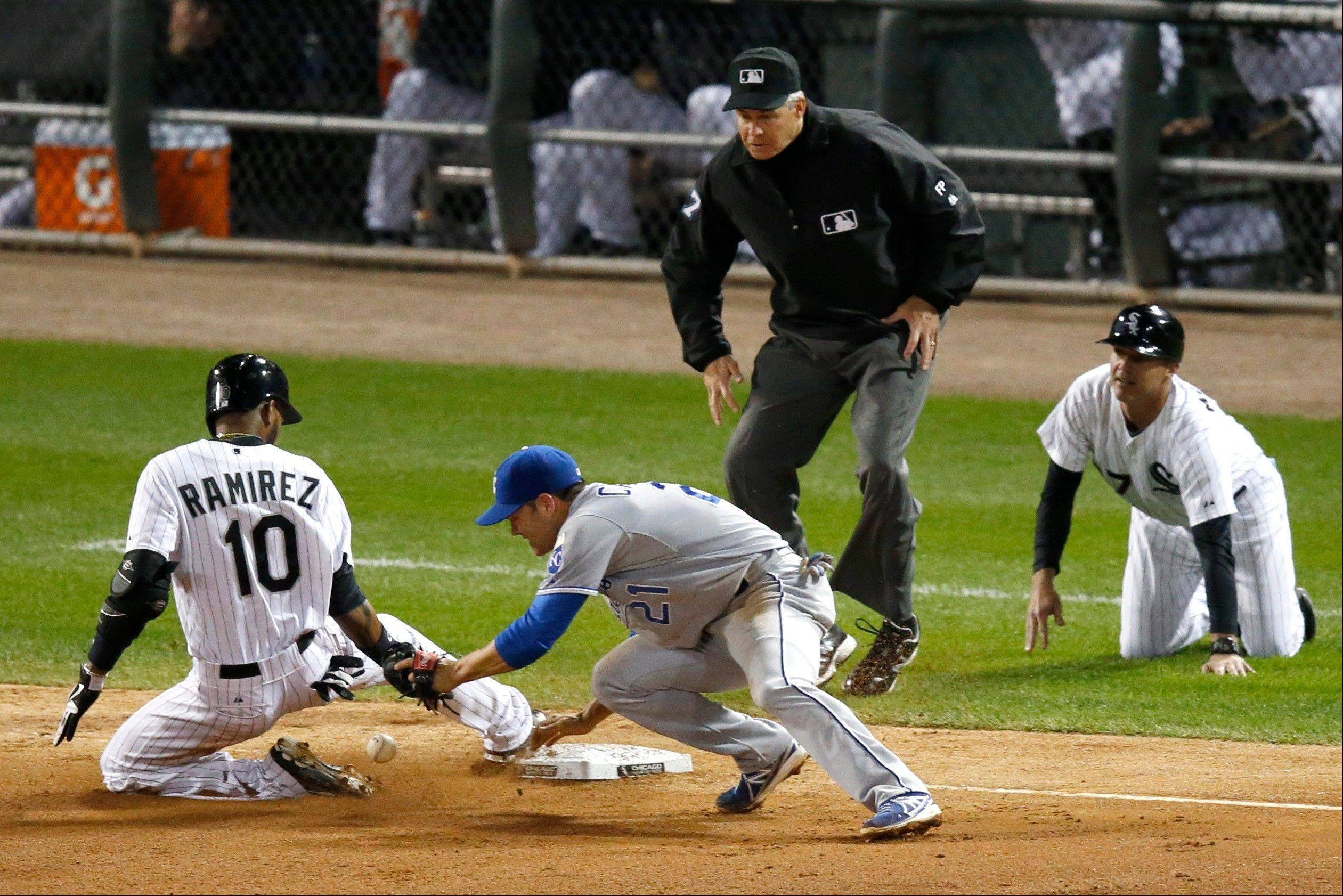Alexei Ramirez slides safely into third past Royals third baseman Jamey Carroll after hitting a triple in the fourth inning Friday in Chicago. Watching on the play are umpire Gary Darling and Sox third base coach Joe McEwing.