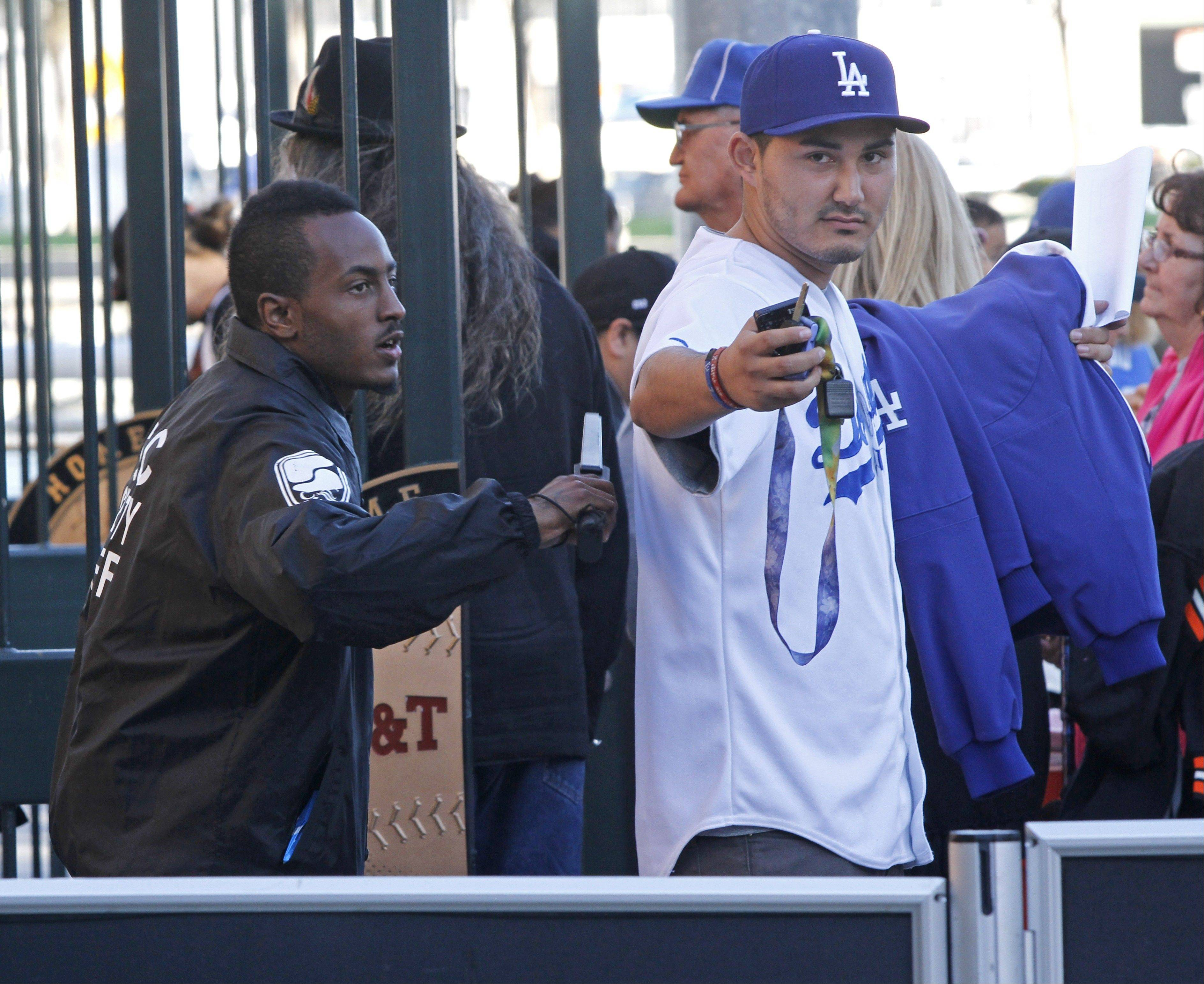 A security guard checks a Los Angeles Dodgers fan at the stadium entrance before Thursday's game between the Giants and the Dodgers in San Francisco.