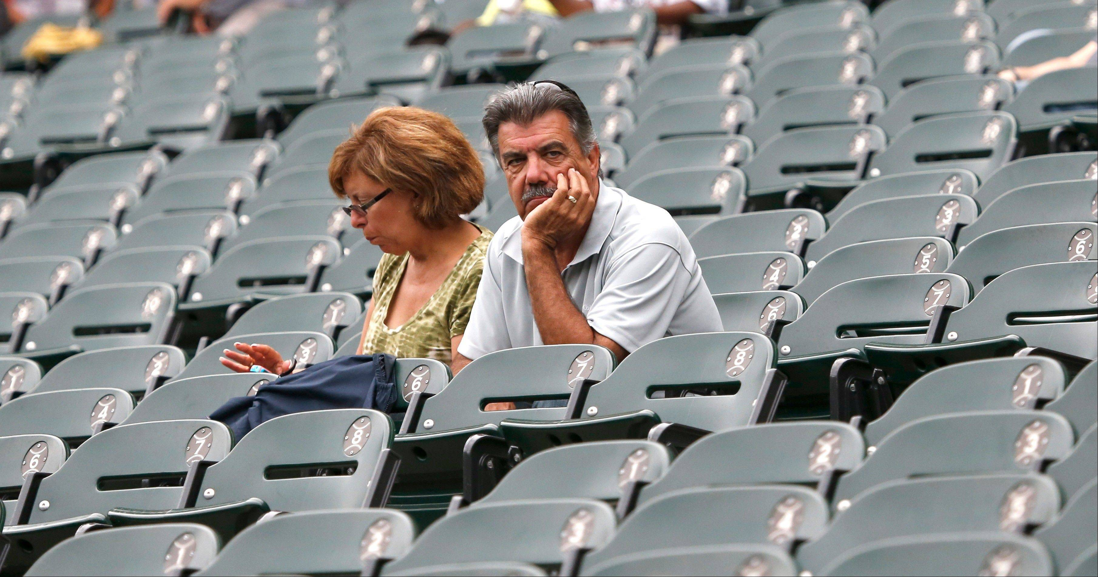 A fan sits head in hand during a game between the Chicago White Sox and Minnesota Twins in Chicago. The White Sox have seen their attendance drop for the seventh straight season since a high of 2.9 million in 2006.