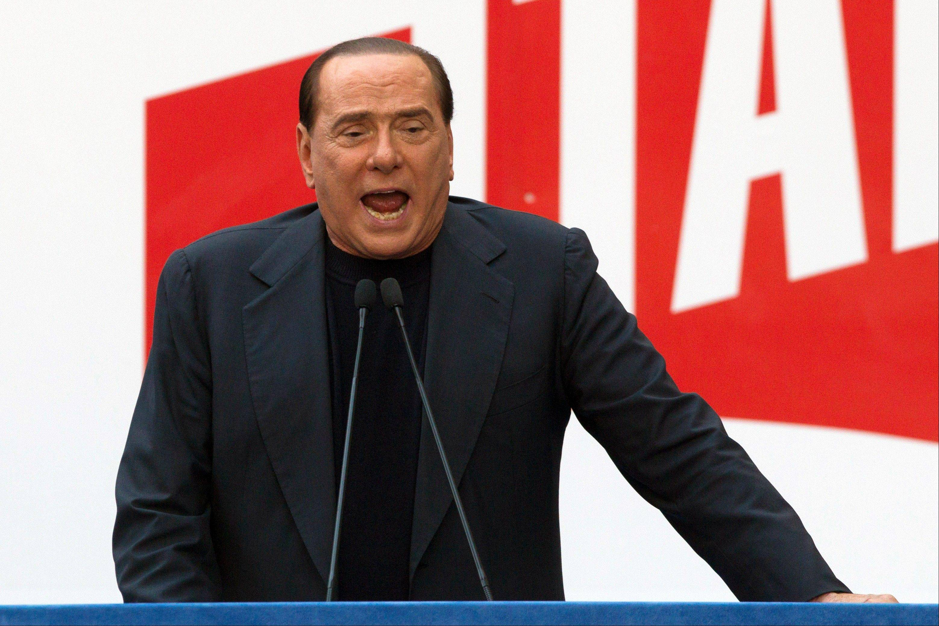 In this Sunday, Aug. 4, 2013 file photo, former Italian Premier Silvio Berlusconi addresses supporters during a demonstration in front of his residence in Rome. Government ministers in former Premier Silvio Berlusconi�s political party have announced Saturday their intention to resign their posts, a move that raises tension in the uneasy coalition government and increases the possibility of early elections. Vice Premier Angelino Alfano�s spokeswoman said Saturday the five ministers from Berlusconi�s center-right People of Freedom Party have decided to submit their resignations.