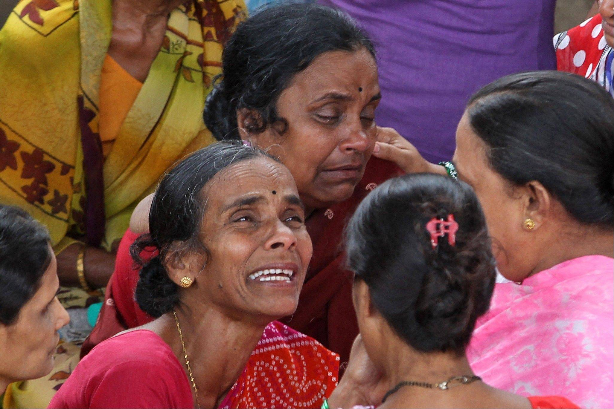 Indian women cry for missing relatives at the site of a building that collapsed, in Mumbai, India, Saturday, Sept. 28. Frantic relatives kept up a vigil at the site of the collapsed apartment building that killed more than 30 people in India's financial capital of Mumbai as the search for survivors grew bleak on Saturday.