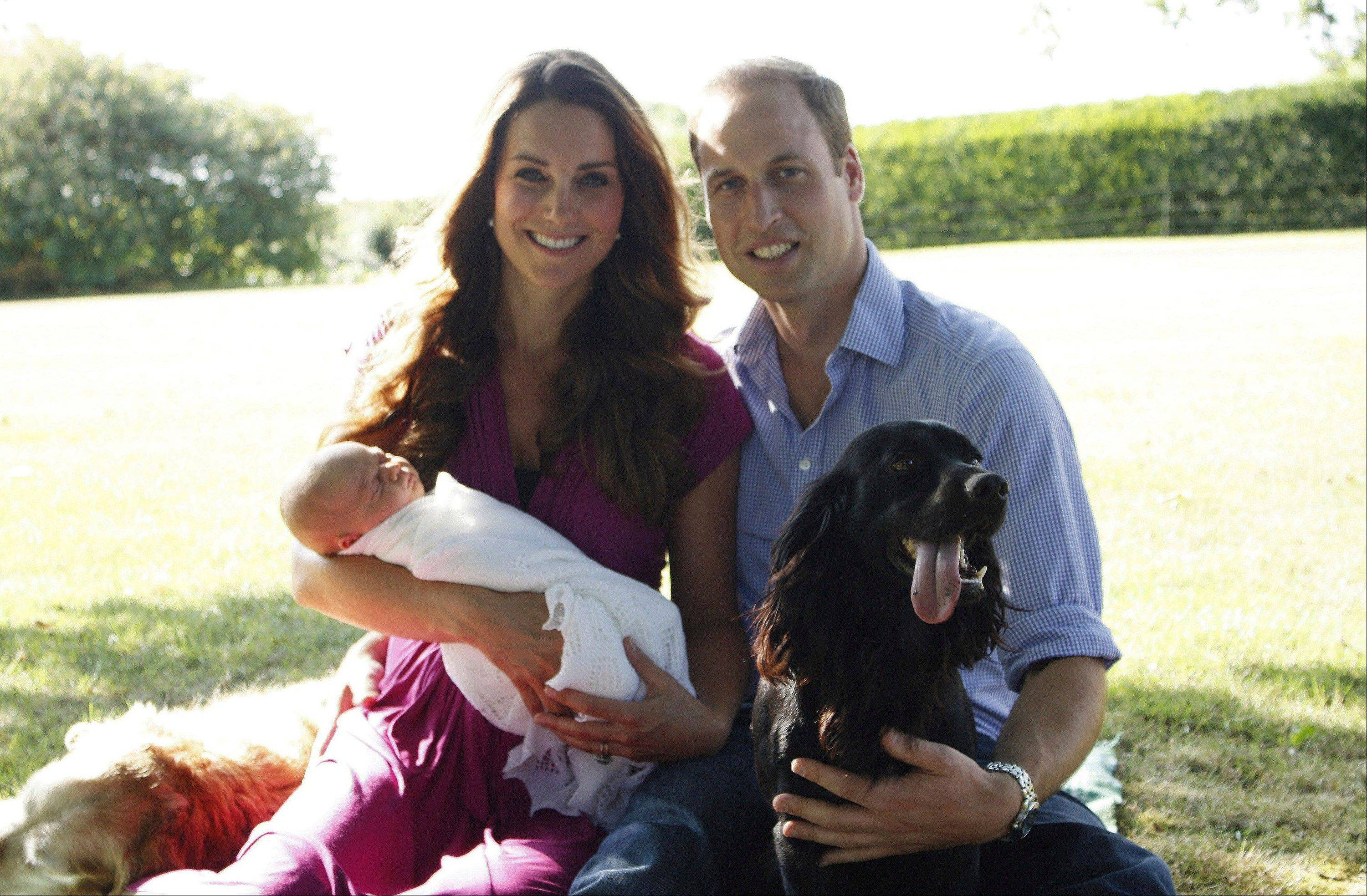 This image taken by Michael Middleton, the Duchess's father, in early August 2013 and supplied by Kensington Palace, shows the Duke and Duchess of Cambridge with their son, Prince George, in the garden of the Middleton family home in Bucklebury, England, with Tilly the retriever, seen left, a Middleton family pet, and Lupo, the couple's cocker spaniel.
