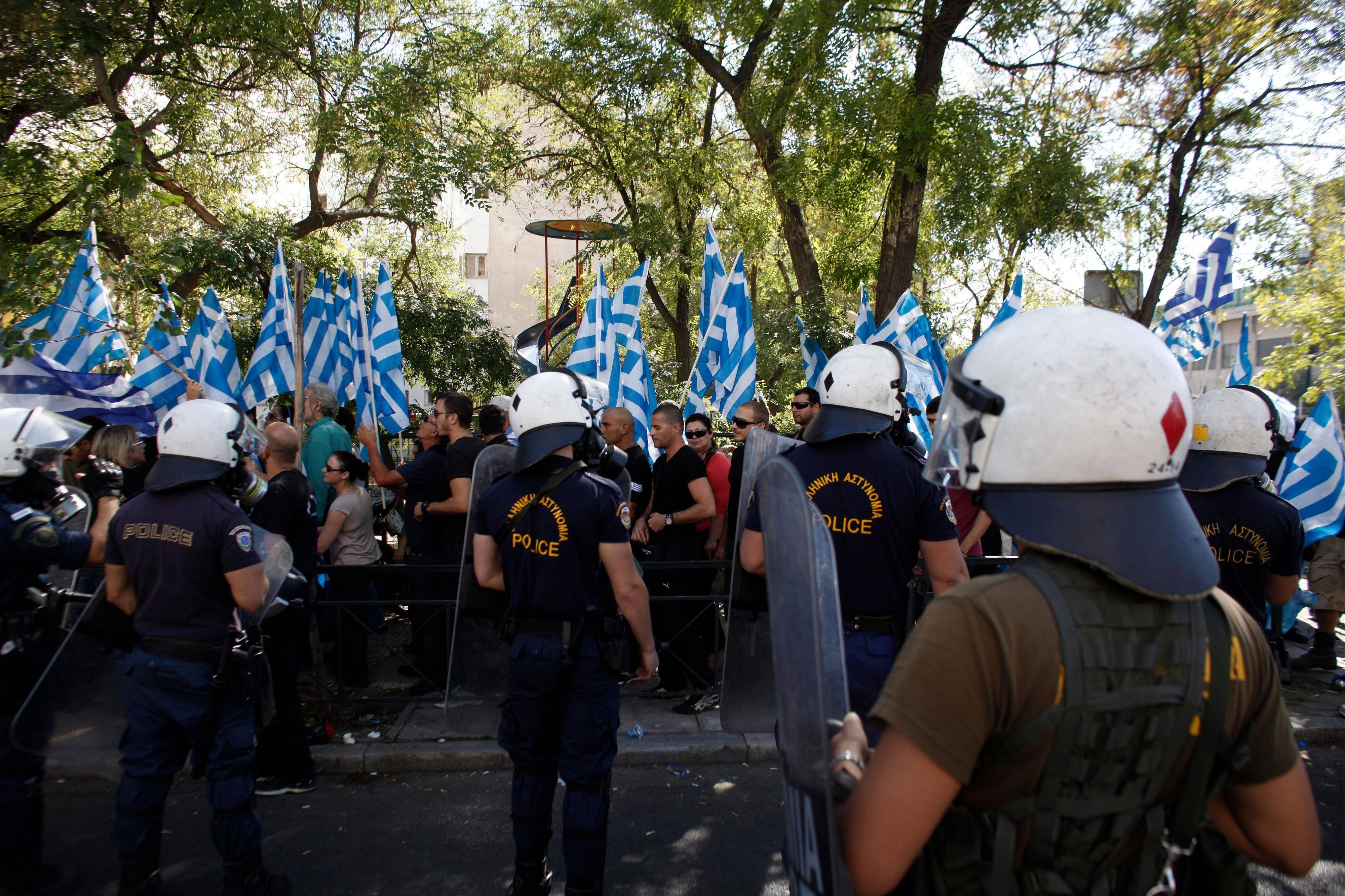 Riot police officers watch supporters of the extreme far-right Golden Dawn party during a protest in solidarity of the arrested lawmakers in front of the headquarters of Greek Police, in Athens, Saturday, Sept. 28. Police arrested the leader of Greece�s extreme-right Golden Dawn party and other top members on Saturday, in an escalation of a government crackdown after a fatal stabbing allegedly committed by a supporter. It is the first time since 1974 that sitting members of Parliament have been arrested.