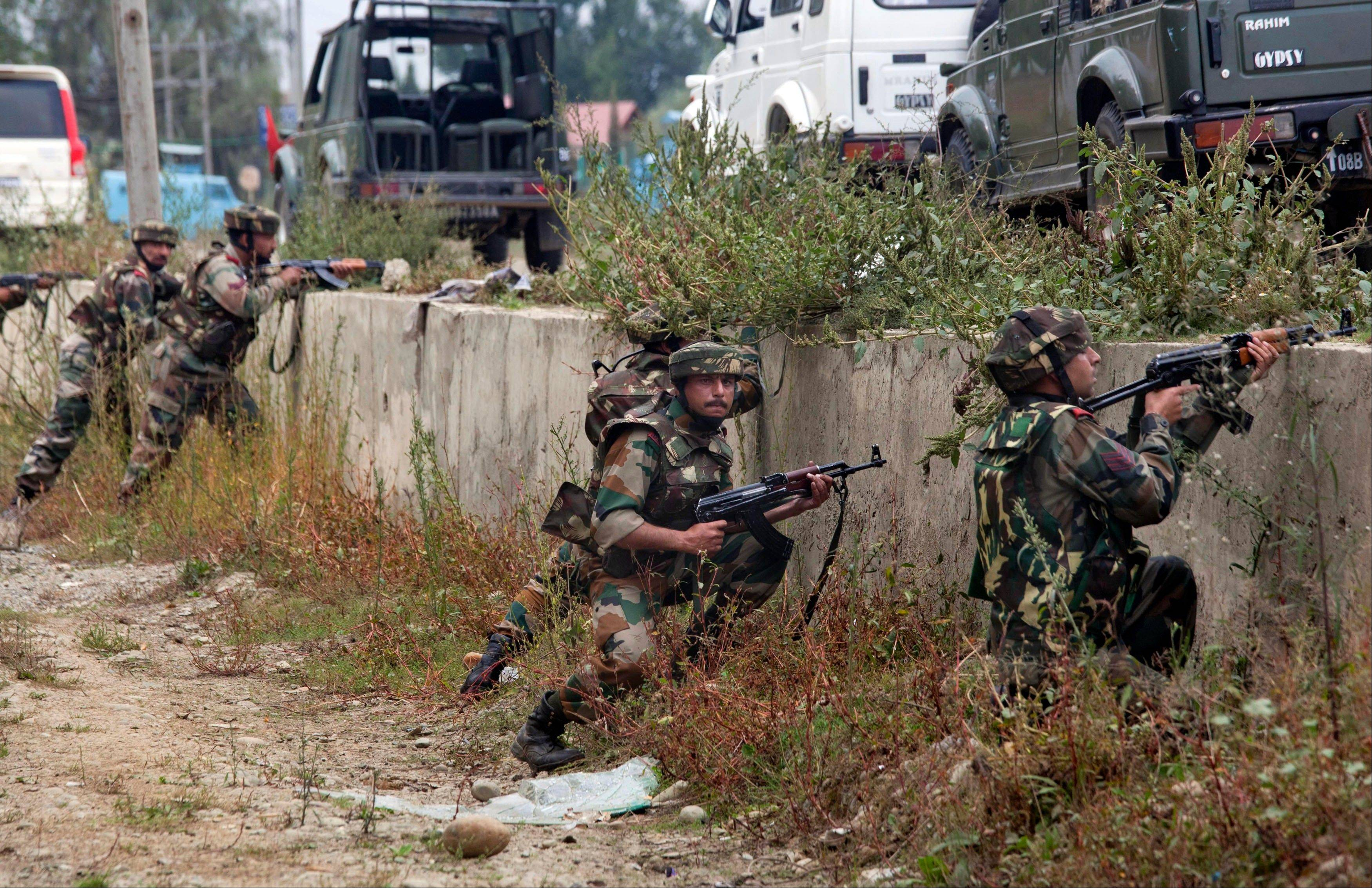 Indian army soldiers take position during a shooting near a military convoy on the outskirts of Srinagar, India, Saturday, Sept. 28. It was not immediately clear if the shots fired Saturday in Srinagar came from two men riding a motorcycle past the convoy, or from patrolling street officers who suspected the men were militants.