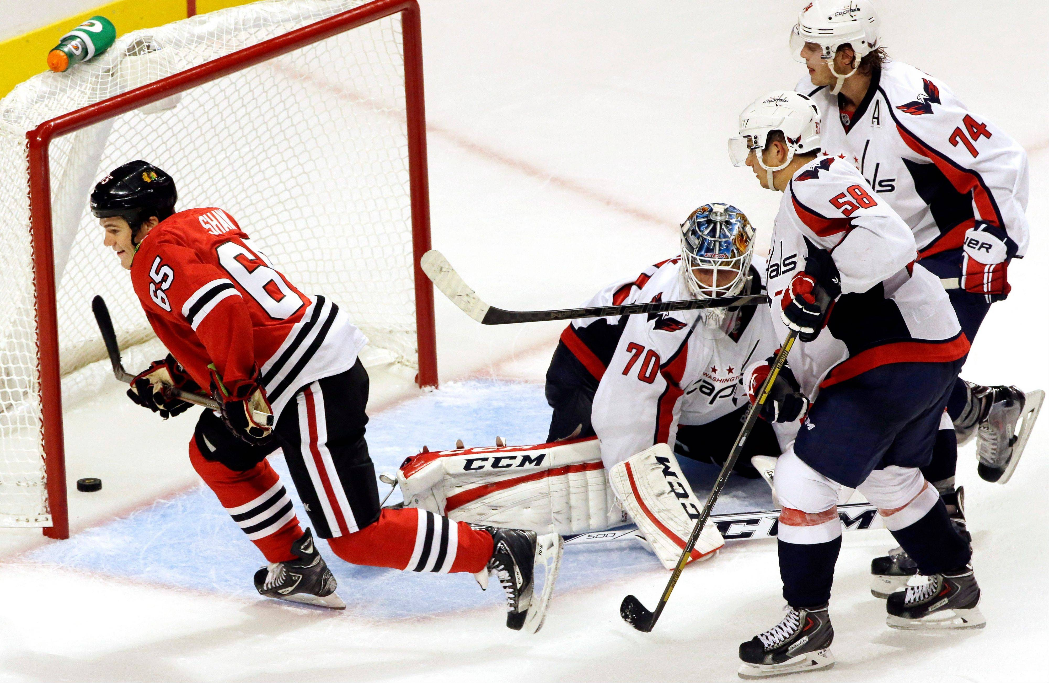 Chicago Blackhawks' Andrew Shaw (65) scores as Washington Capitals goalie Braden Holtby (70), Connor Carrick (58) and John Carlson (74) react during overtime of an NHL preseason hockey game in Chicago Saturday. The Blackhawks won 4-3.