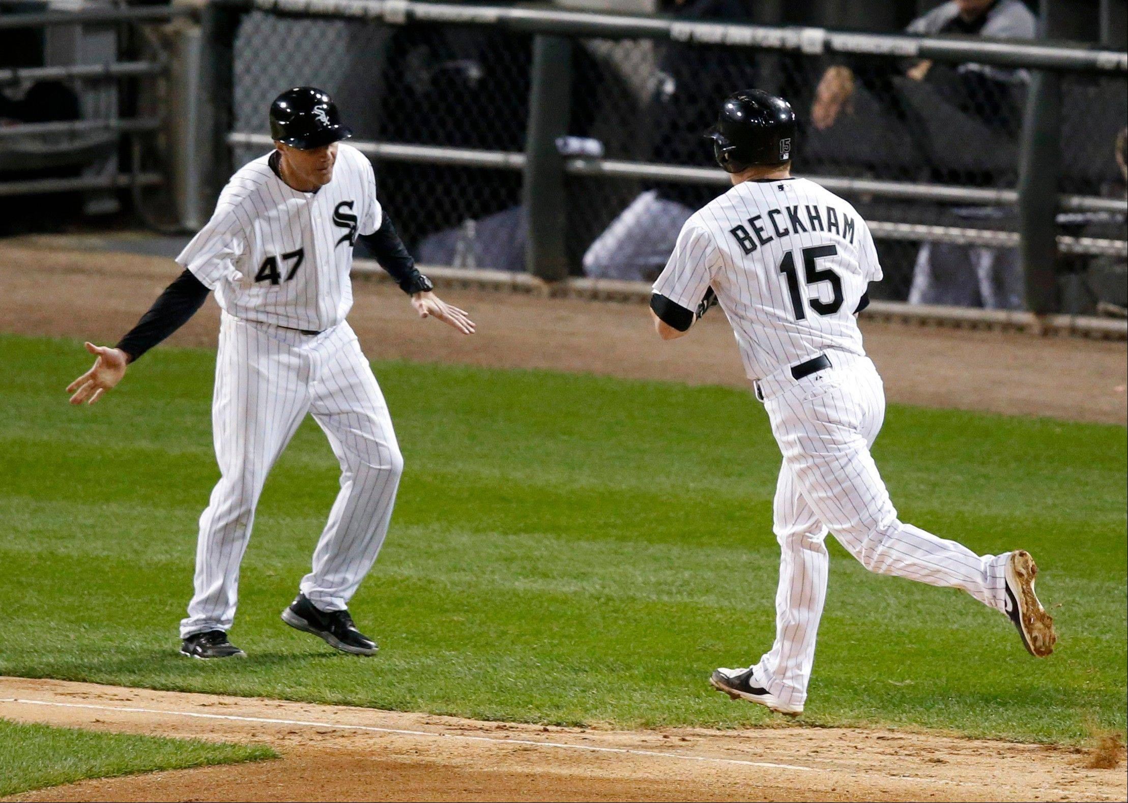 White Sox third base coach Joe McEwing (47) greets Gordon Beckham at third after Beckham's home run off Kansas City Royals starting pitcher James Shields during the sixth inning of a baseball game Friday, Sept. 27, 2013, in Chicago. (AP Photo/Charles Rex Arbogast)