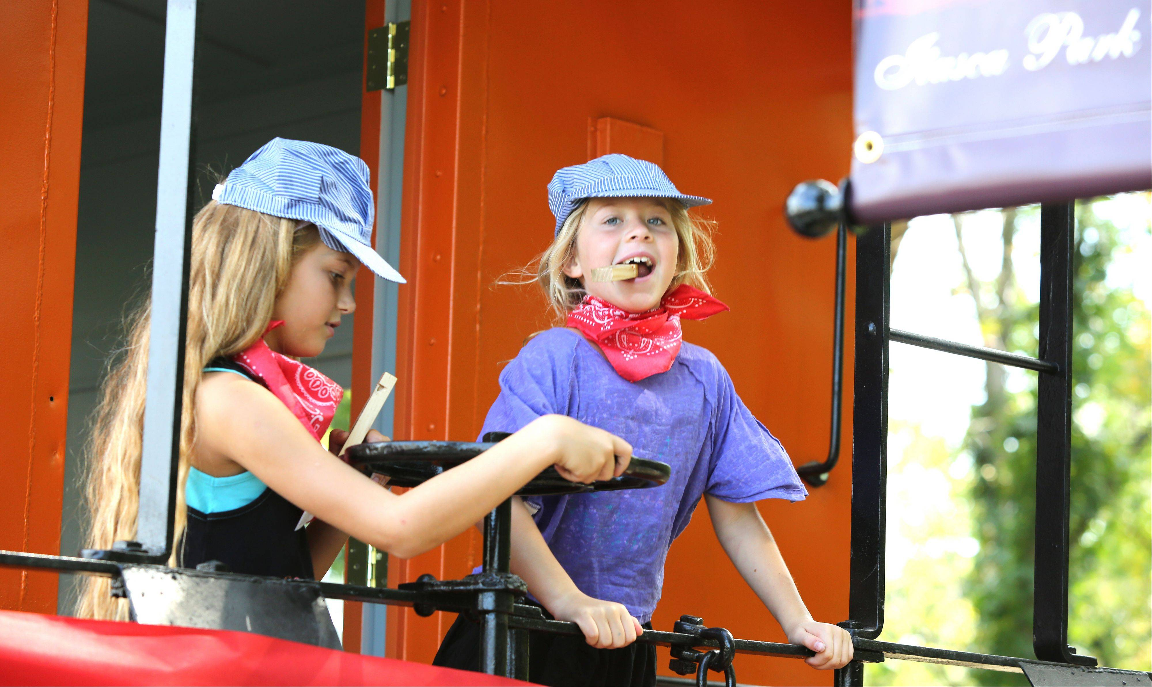 Mallory Leno, 8, left and Hannah Gelinas, 8, right, both of Arlington Heights, tour a 74-year-old newly restored caboose as the Itasca Historical Depot Museum hosts its grand reopening event.