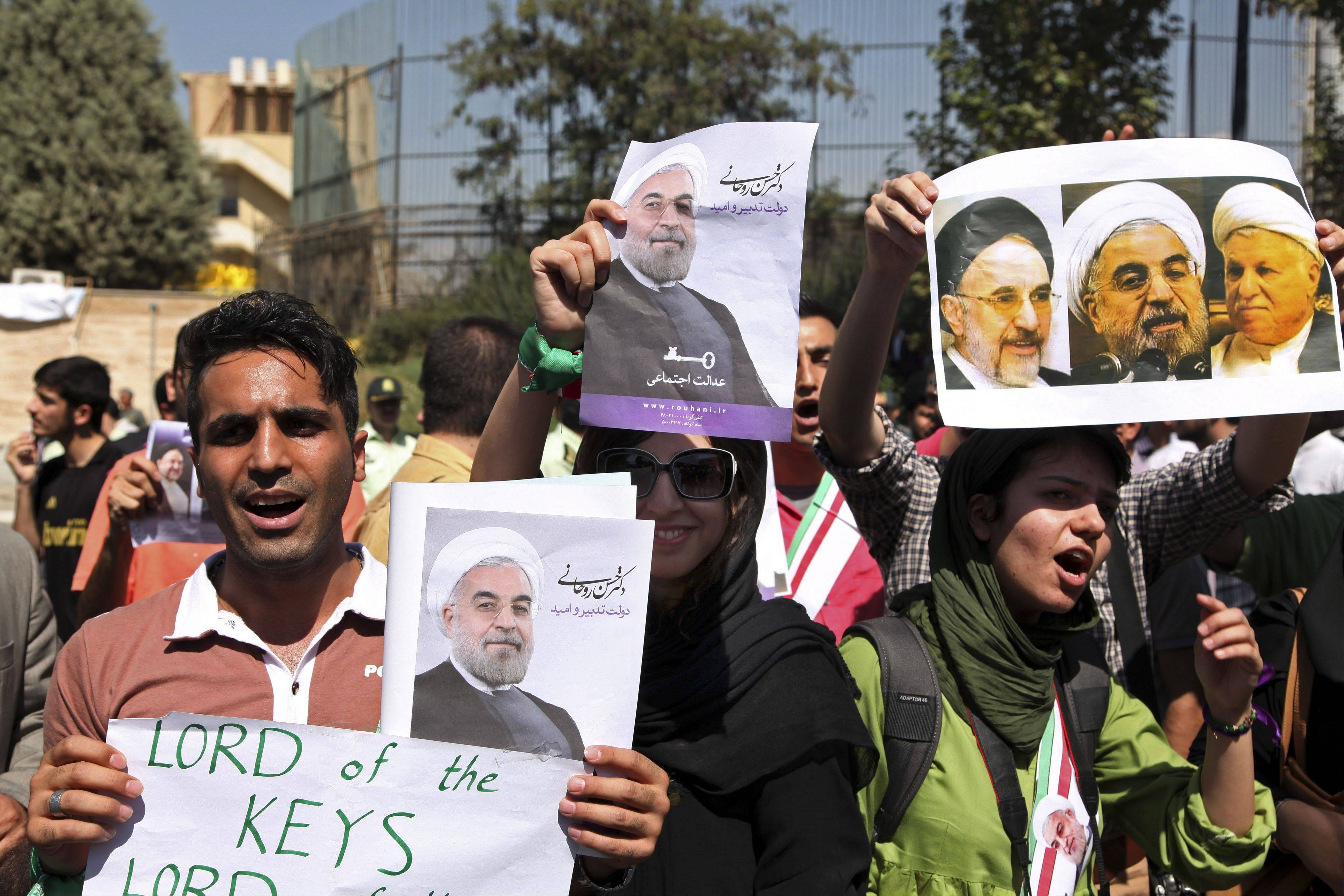 Supporters of Iranian President Hassan Rouhani, hold posters with photos of him, upon his arrival from the U.S. near the Mehrabad airport in Tehran, Iran, Saturday, Sept. 28. Iranians from across the political spectrum hailed Saturday the historic phone conversation between President Barack Obama and Rouhani, reflecting wide support for an initiative that has the backing of both reformists and the country's conservative clerical leadership.