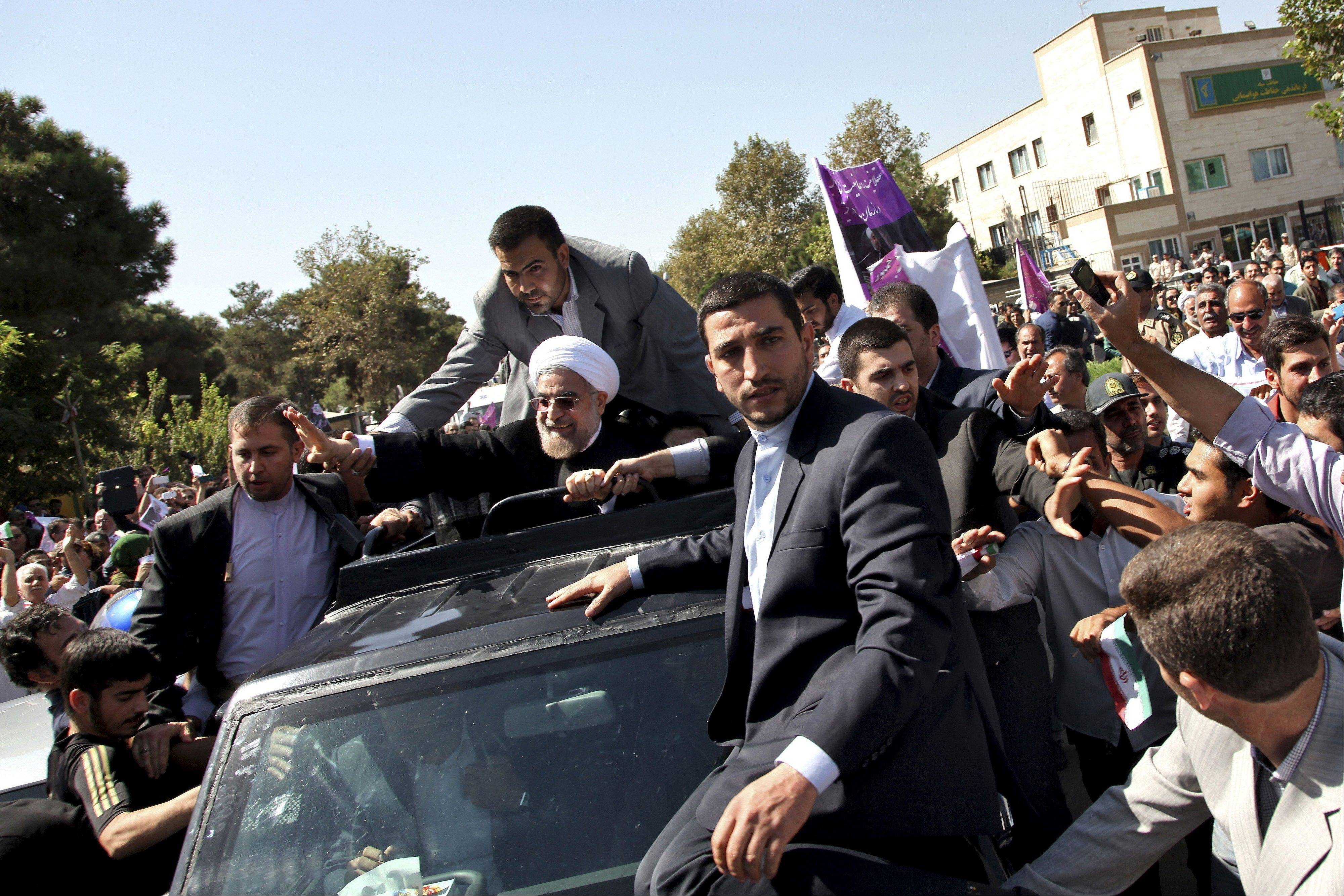 Iranian President Hassan Rouhani, center, waves to supporters upon his arrival from the US near the Mehrabad airport in Tehran, Iran, Saturday, Sept. 28. Iranians from across the political spectrum hailed Saturday the historic phone conversation between President Barack Obama and Rouhani, reflecting wide support for an initiative that has the backing of both reformists and the country's conservative clerical leadership.
