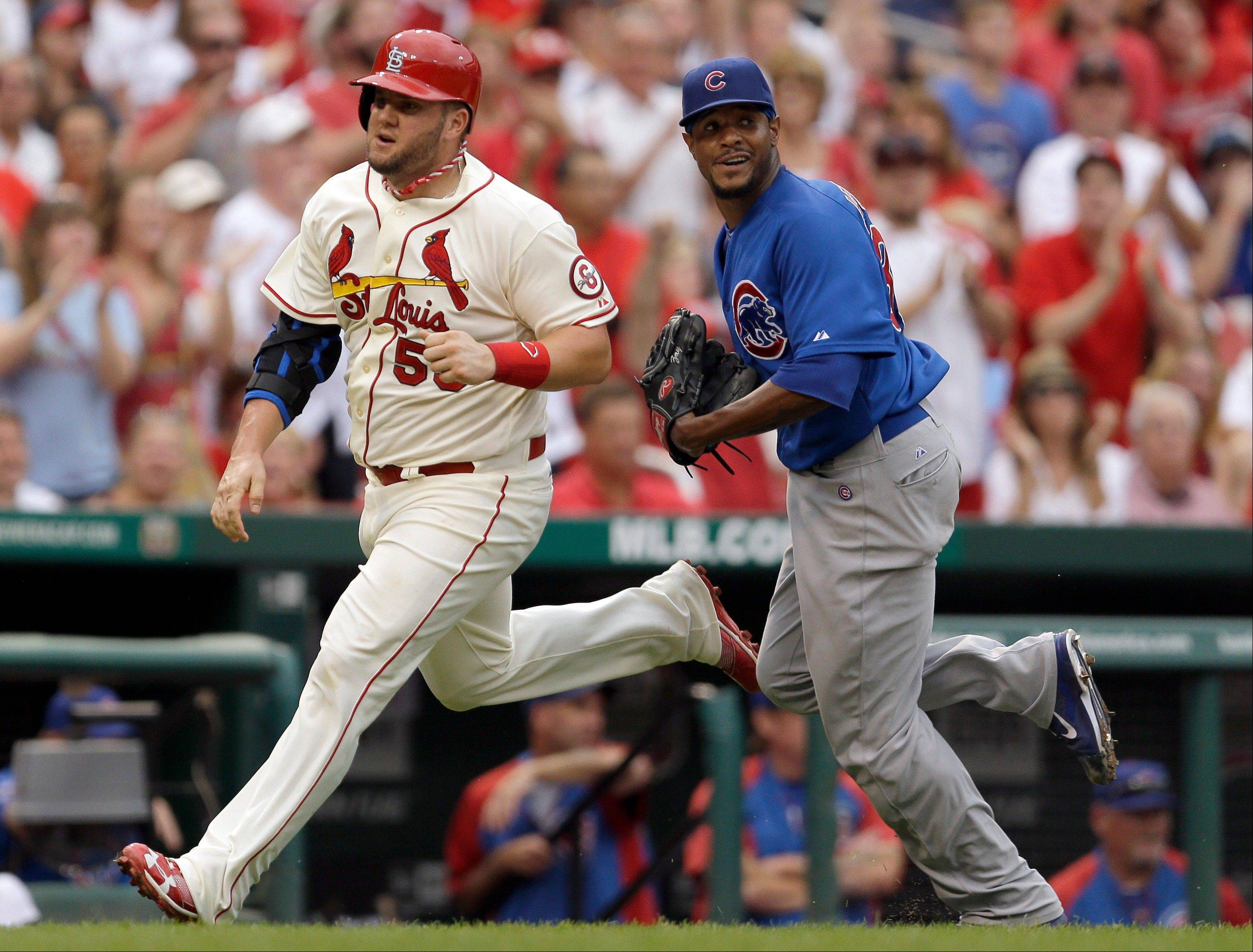 St. Louis Cardinals' Matt Adams, left, heads in to score on a two-run double by Yadier Molina as Chicago Cubs starting pitcher Edwin Jackson, right, runs to back up the throw during the third inning of a baseball game Saturday in St. Louis.