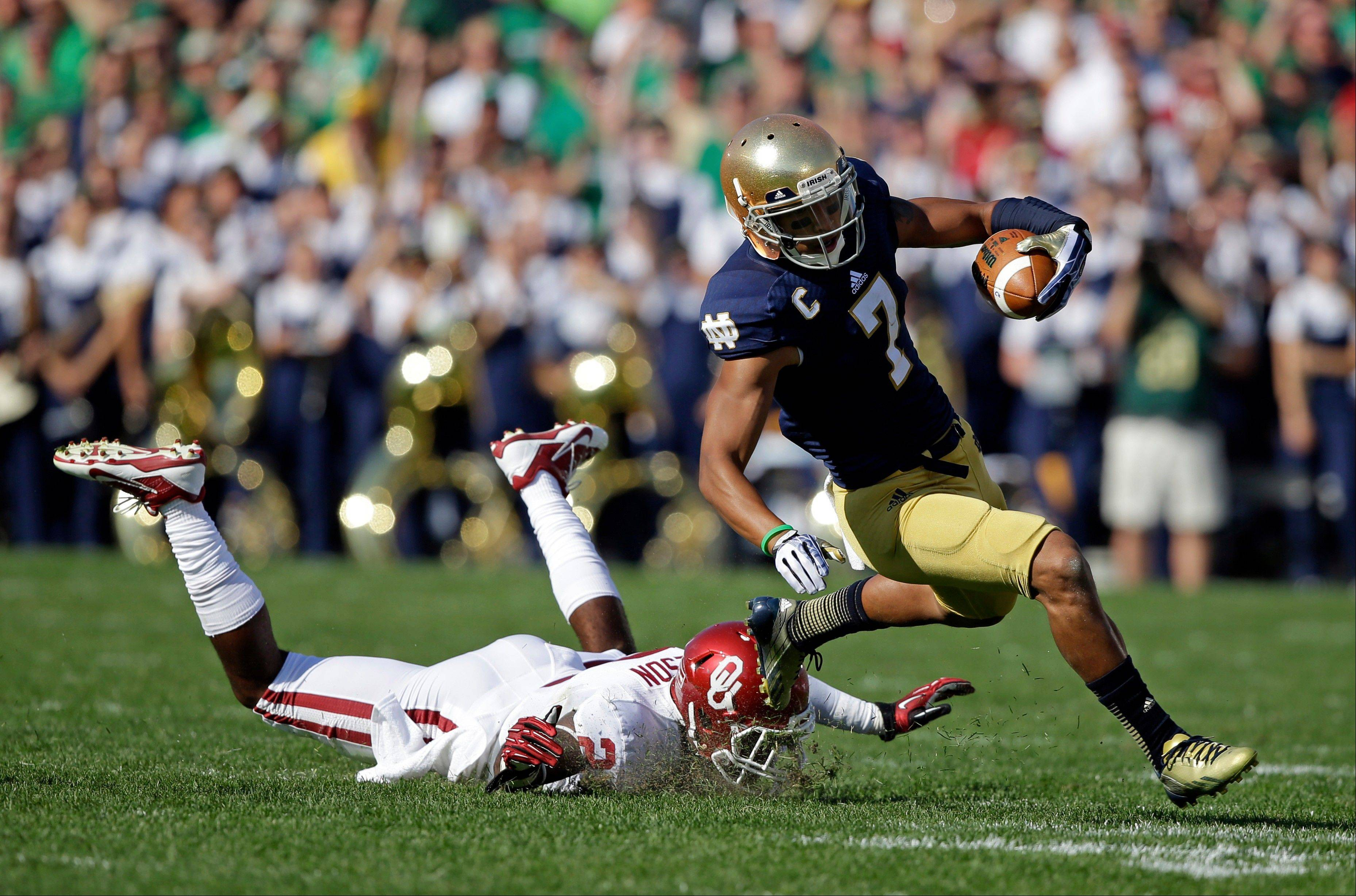 Oklahoma's Julian Wilson (2) tackles Notre Dame's TJ Jones (7) during the first half Saturday in South Bend, Ind.