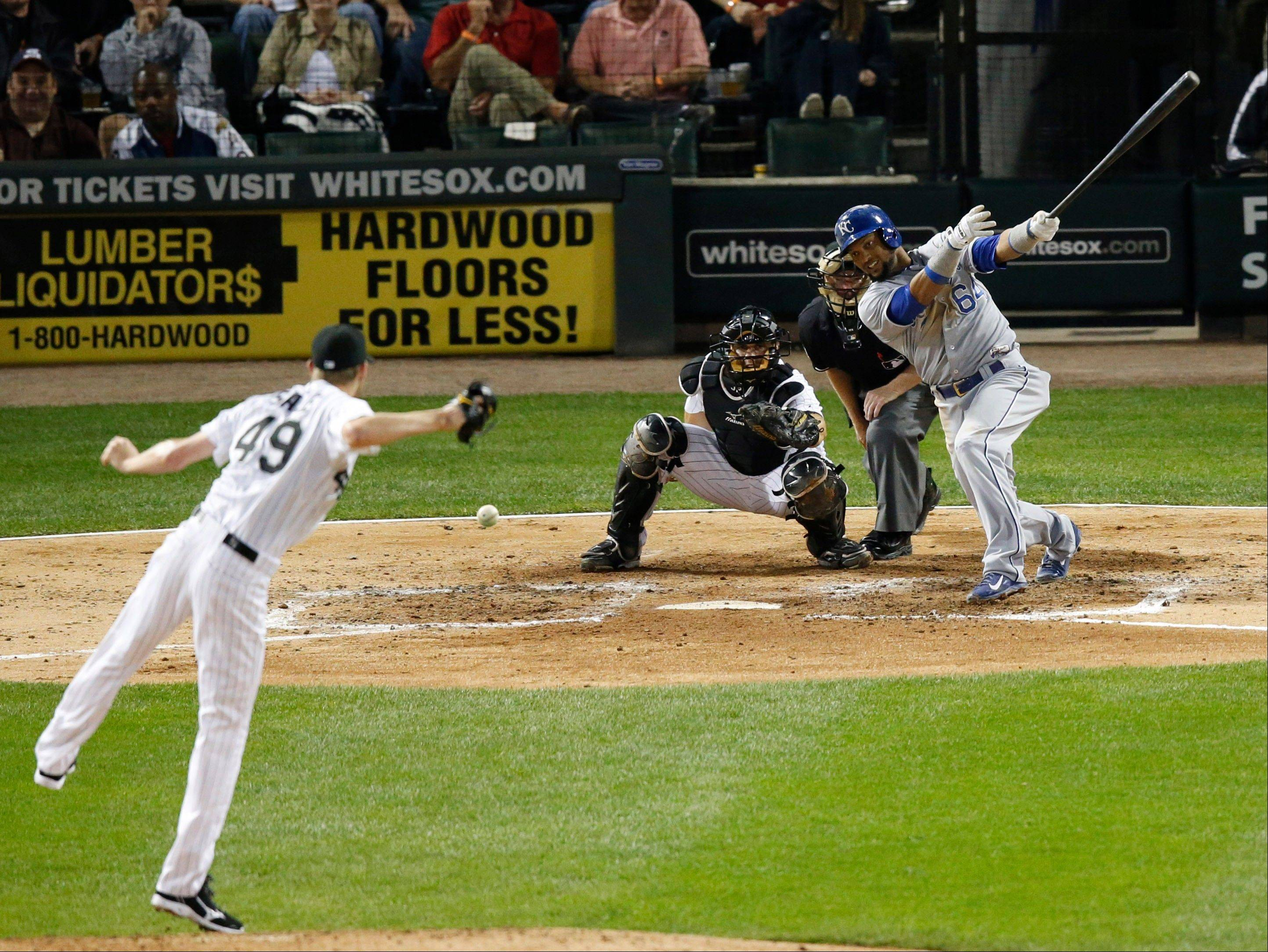 Kansas City Royals' Emilio Bonifacio, right, hits an RBI single past Chicago White Sox starting pitcher Chris Sale during the fourth inning of a baseball game Friday, Sept. 27, 2013, in Chicago.