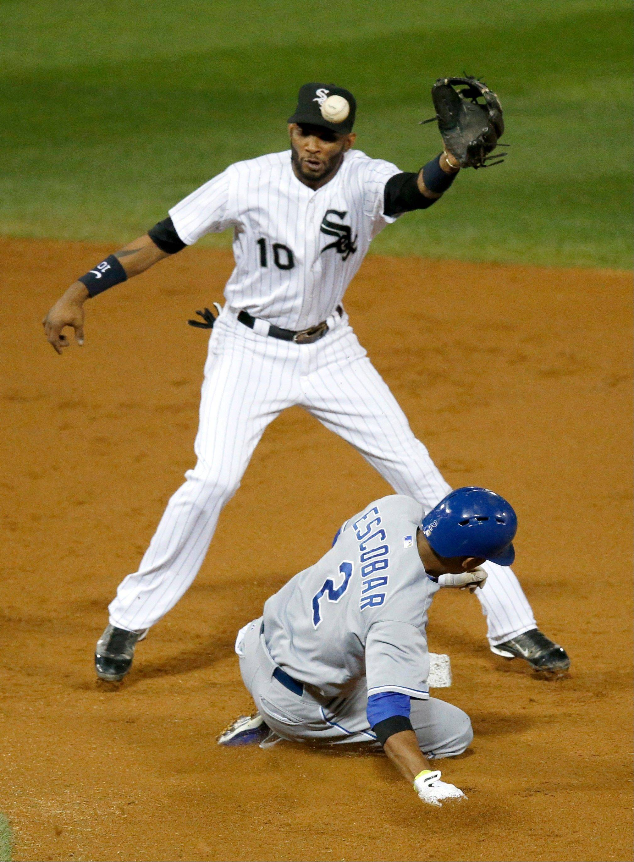 Kansas City Royals' Alcides Escobar (2) steals second on a throw from Chicago White Sox catcher Josh Phegley to shortstop Alexei Ramirez during the second inning of a baseball game Friday, Sept. 27, 2013, in Chicago.