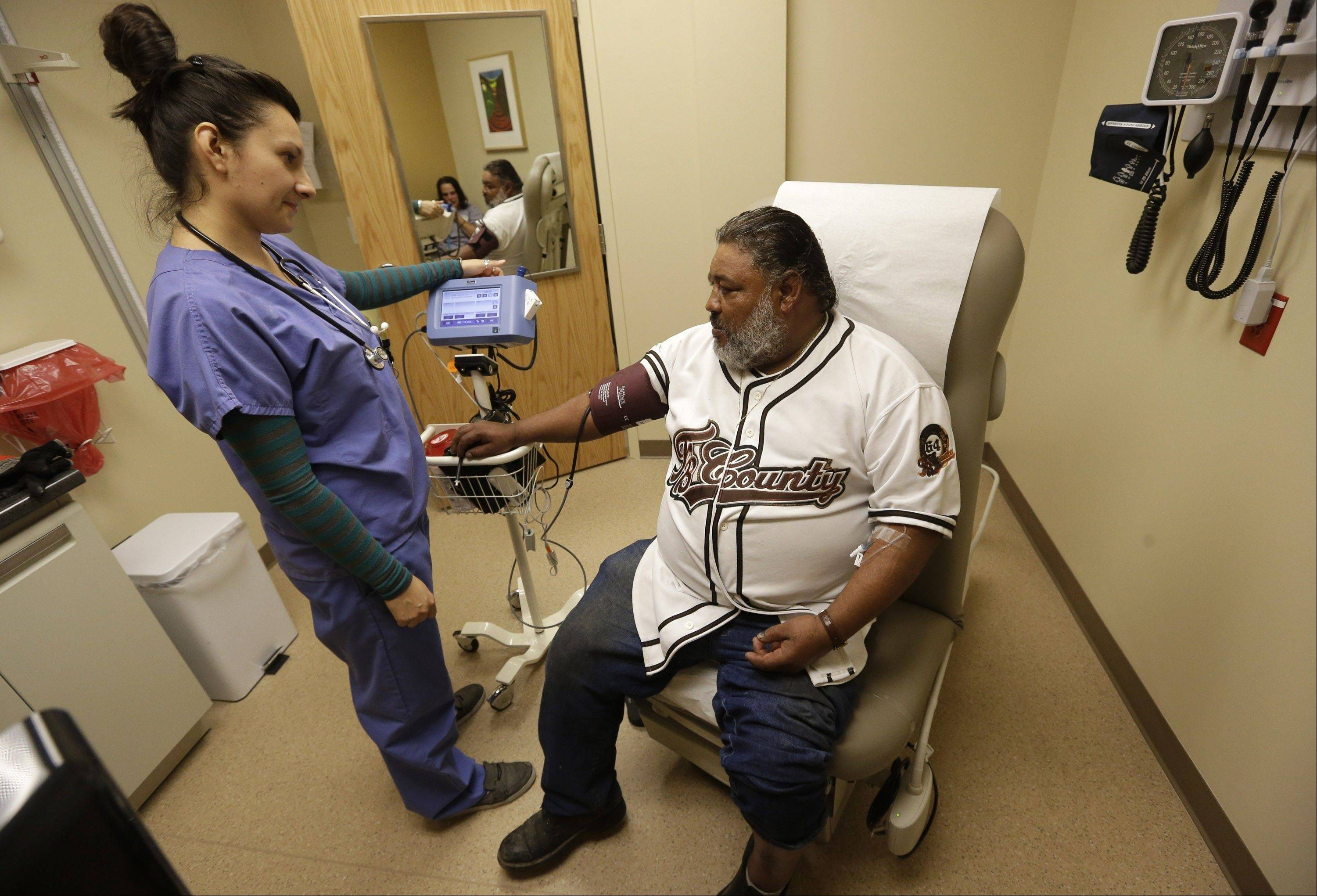 Medical assistant Angelica Colmenero takes the blood pressure of Jose Martinez at the 4th Street Clinic Wednesday in Salt Lake City. In Utah and across the country, new online insurance marketplaces are scheduled to open for business Tuesday as part of the new federal health overhaul.
