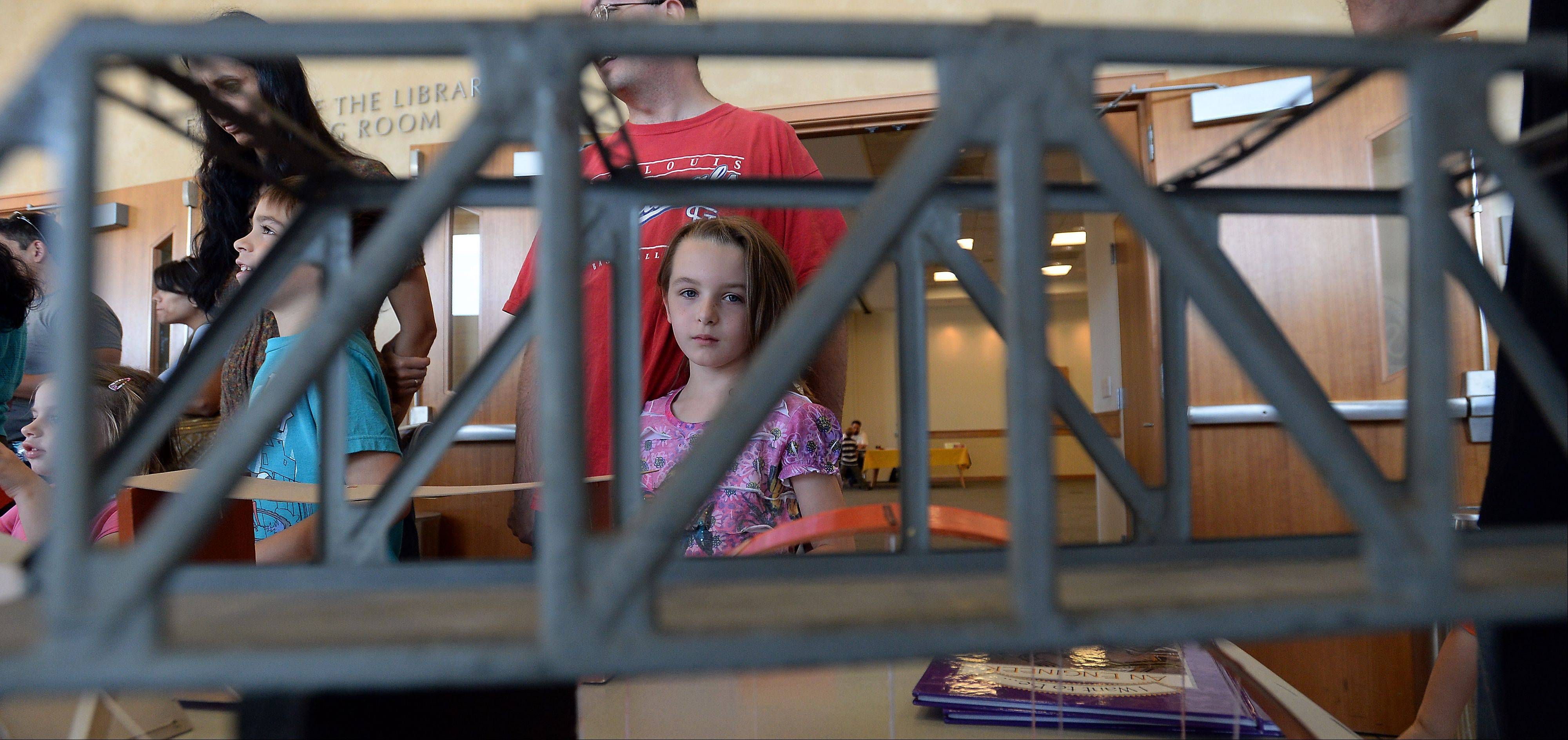 Jora Usher, 6, of Rolling Meadows looks at one of the bridge designs at the fifth-annual Family Science Expo at the Des Plaines Public Library Saturday.