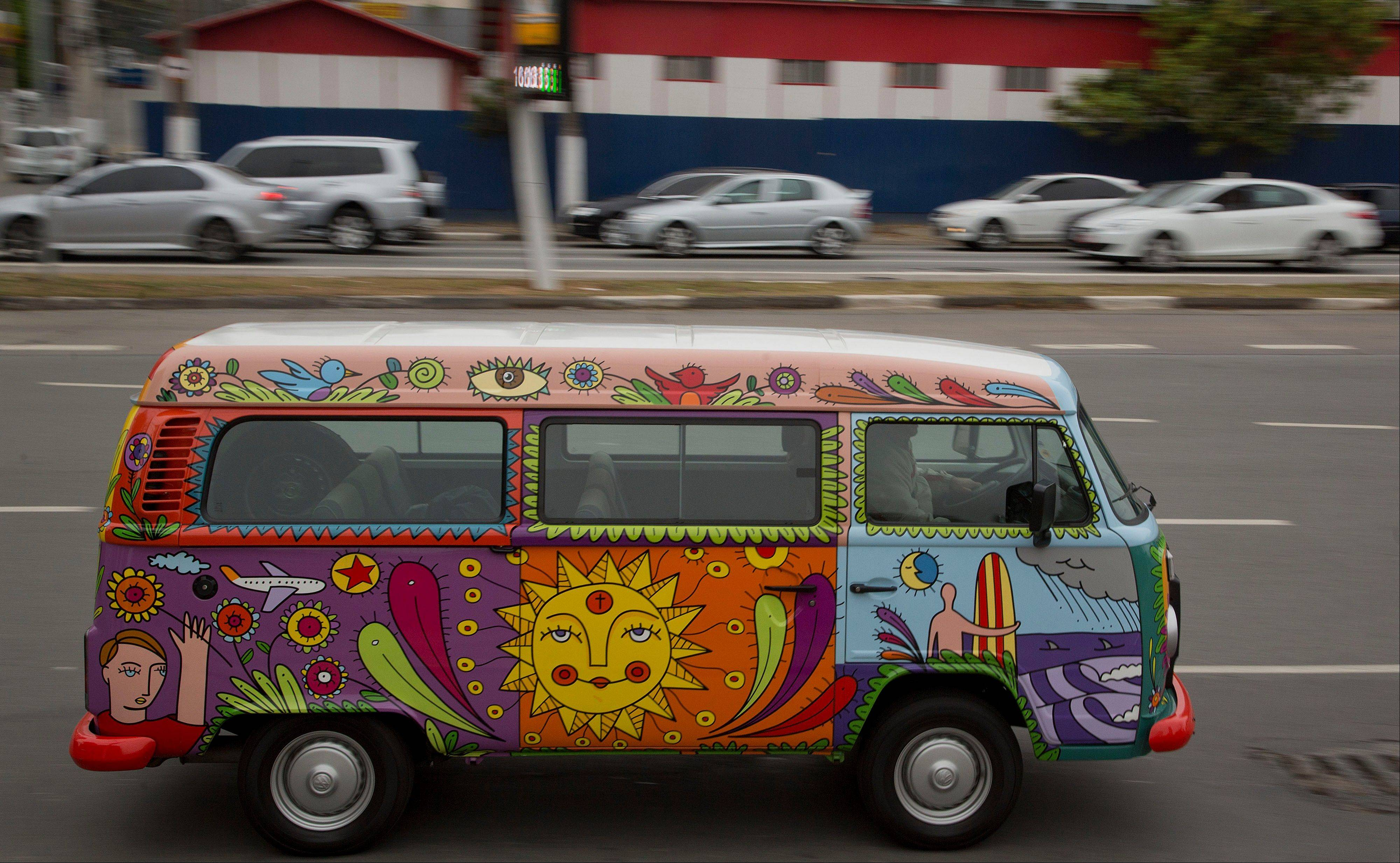 "Advertising executive Marcelo Serpa drives his Volkswagen van, or Kombi, emblazoned with a ""rolling mural,"" that he painted, through the streets of Sao Paulo, Brazil. Serpa's 2007 VW van version is meant to have a 1960s American hippie feel. He painted it in bright green, yellow, blue and red colors with cartoonlike drawings of his wife, daughters, and himself, surfboard in hand. Serpa said the bus evokes ""a spirit of playfulness and happiness,"" causing people to pause and smile when he drives it down Sao Paulo's chaotic streets."