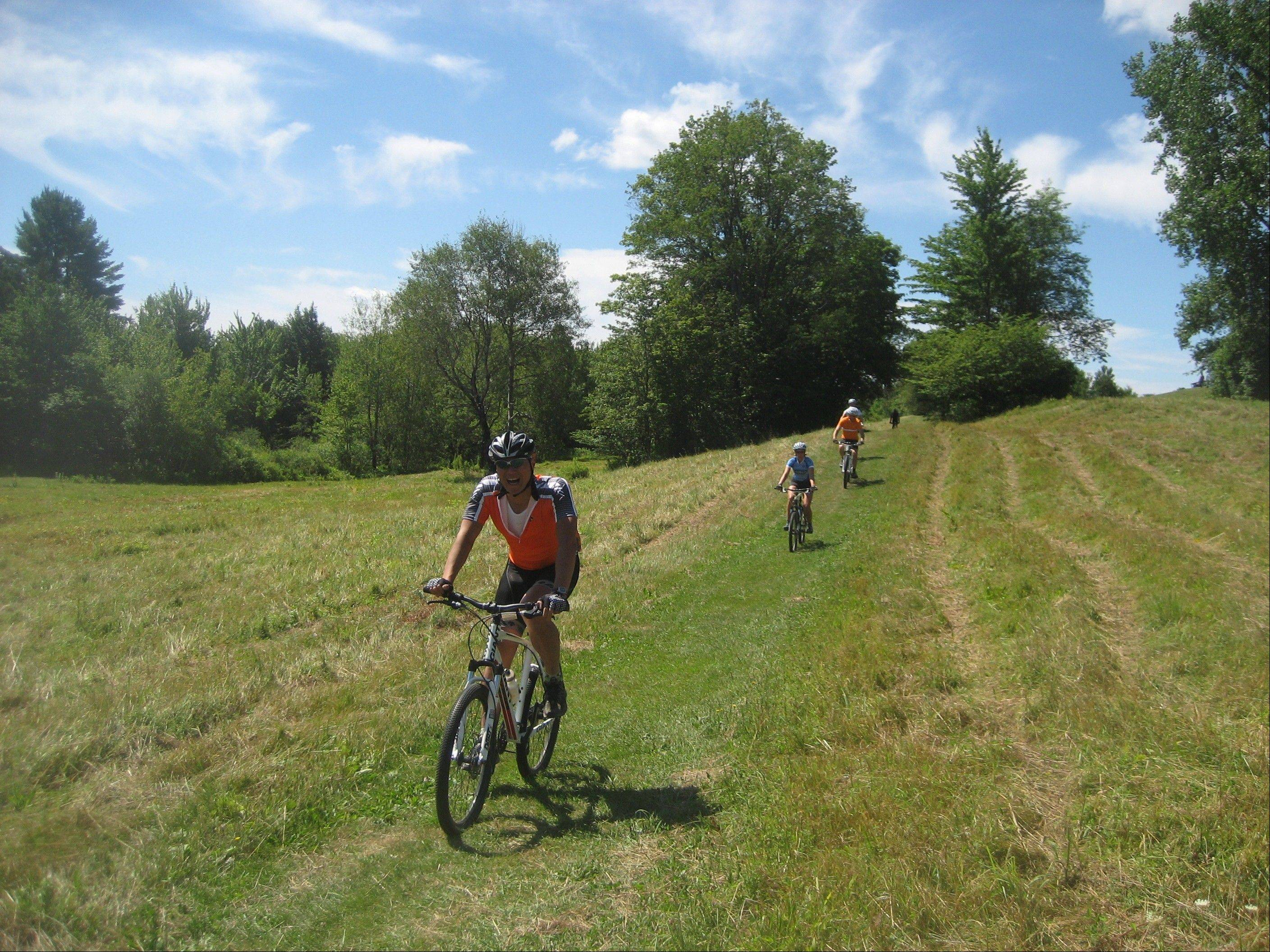 Cyclists on the Vermont Bike & Brew Tour cut through a field.