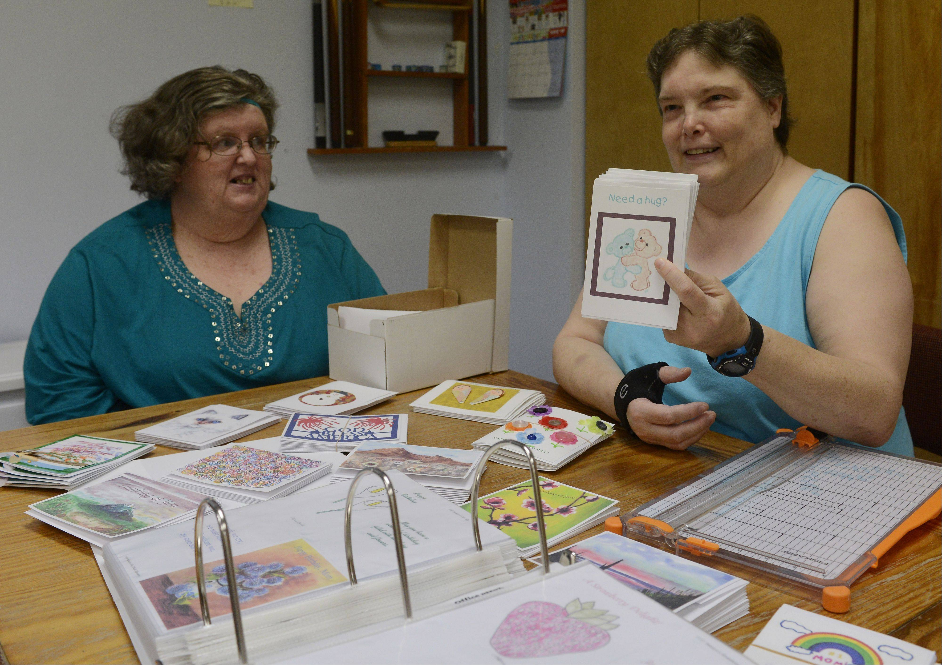 Artists and managers in a not-for-profit greeting card business run by people with mental illnesses, Mary Phelan, left, and Ginger Brooks show off a variety of cards from The Card Project's vast inventory. Sales of greeting cards, right, help with the recovery process at the Kenneth Young Center in Elk Grove Village.